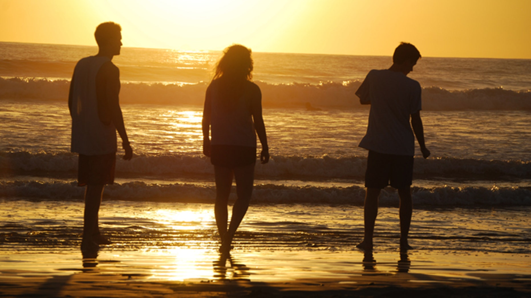 This February 2014 photo released by Kristina MacKulin shows, from left, Liam Godfrey-Jolicoeur, Ruby Dombek and Jacob Dombek of N. Ferrisburg Vt. watching the sunset at Playa Guiones in Nosara, Costa Rica. Nosara is a scenic coastal region with a variety of outdoor recreation activities for visitors. (AP Photo/Kristina MacKulin)