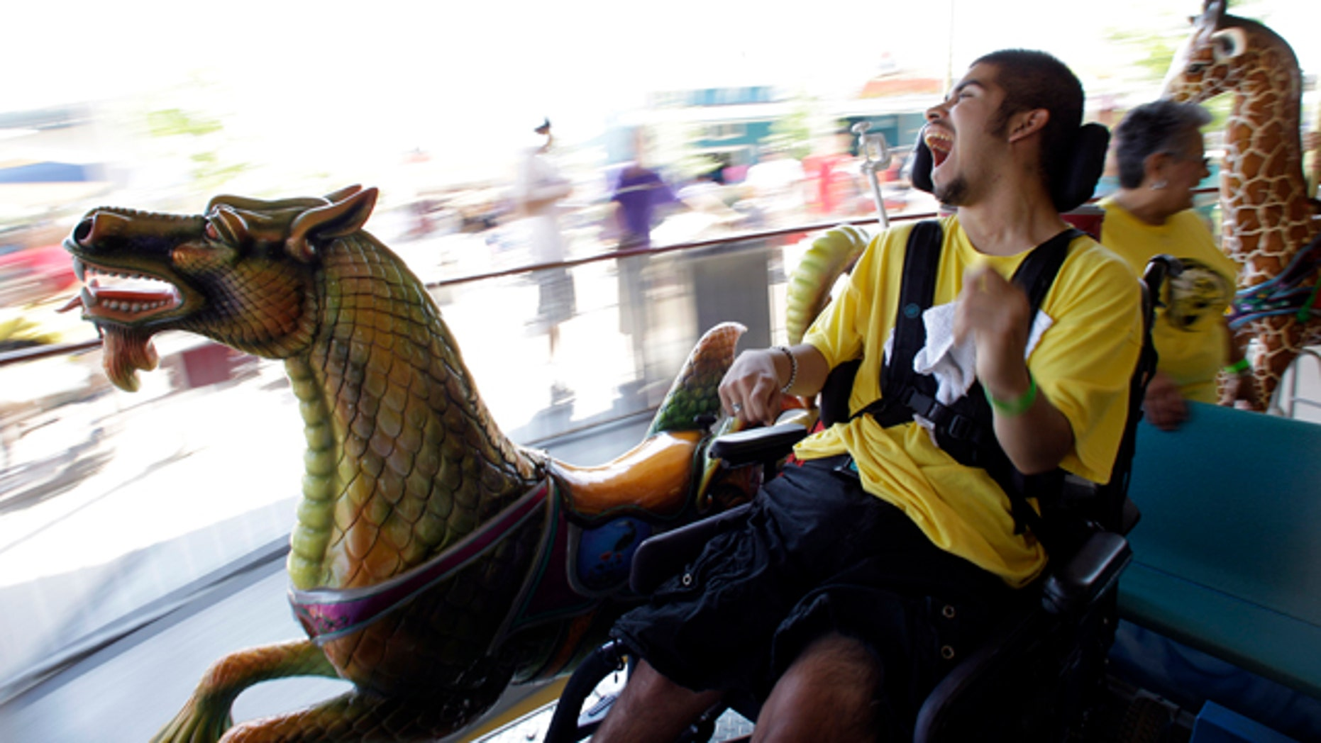 """This Friday, April 29, 2011 photo shows Fabian Mendoza as he rides a carousel at Morgan's Wonderland in San Antonio, Texas. The carousel allows children and adults of different abilities to experience a merry-go-round.   The 25-acre, $34 million park caters every detail to people with physical or mental disabilities, down to jungle gyms wide enough to fit two wheelchairs side-by-side, a """"Sensory Village"""" thats an indoor mall of touch-and-hear activities, and daily attendance limits so the park never gets too loud or lines too long.   (AP Photo/Eric Gay)"""