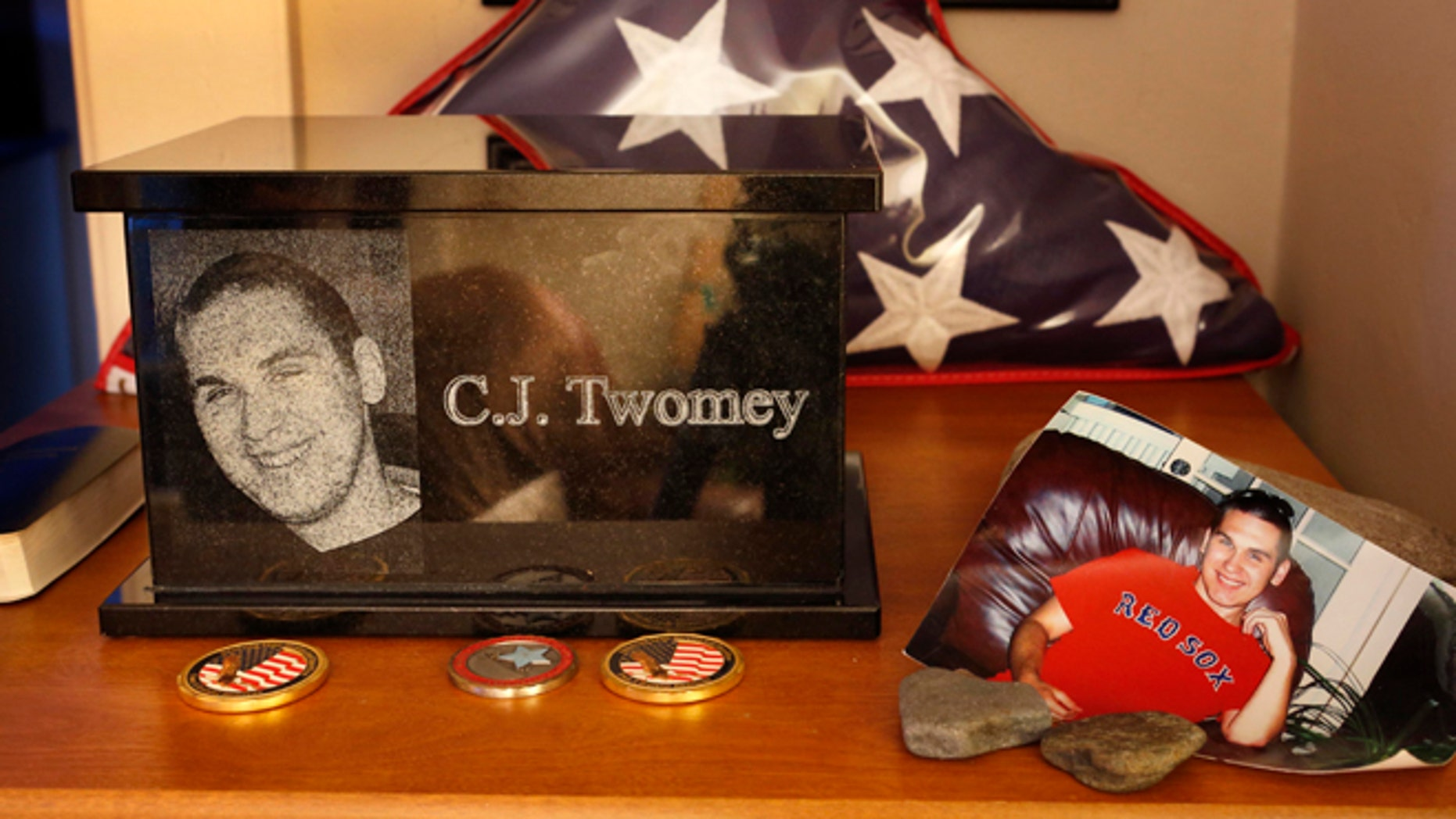 This Dec. 17, 2013, photo shows an urn containing the ashes of C.J. Twomey on a shelf at his parent's home in Auburn, Maine. C.J.'s mother, Hallie Twomey, is asking people to help scatter his ashes throughout the world so he can become part of the world he never got to see.