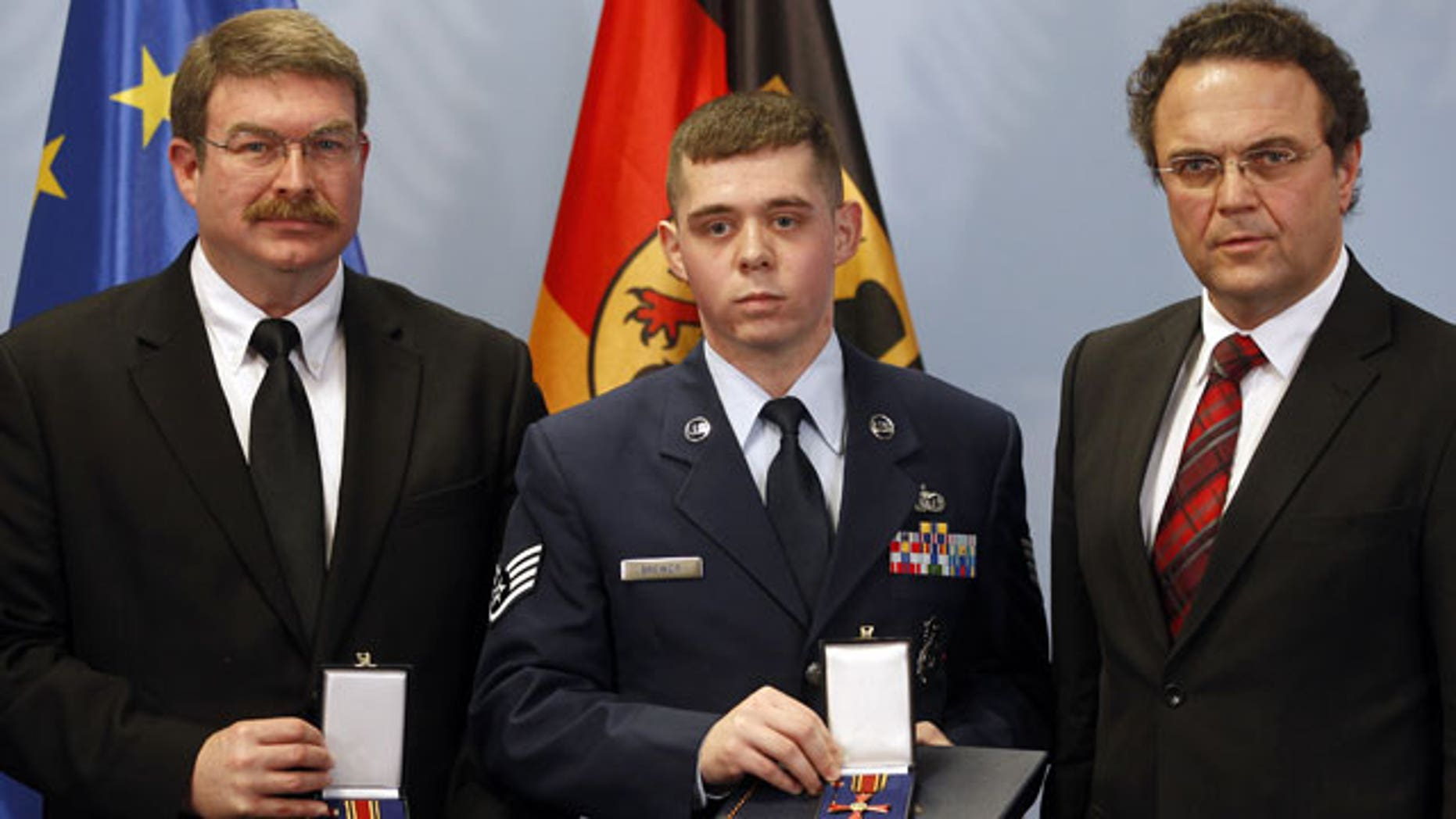 January 16, 2012: Frankfurt airport employee Lamar Joseph Connor, left, from Altha, Florida, and US Staff Sergeant Trevor Donald Brewer, center, from Gray, Tennessee are awarded with The Cross of Merit of the Federal Republic of Germany by German Interior Minister Hans-Peter Friedrich , right, in Berlin, Germany.