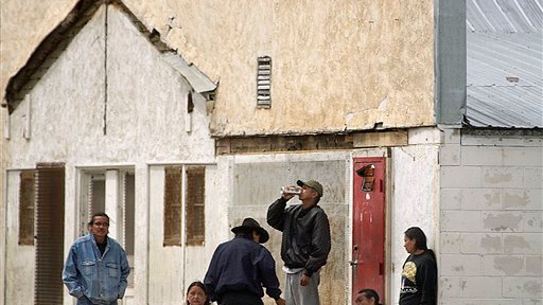 June 7, 2003: A man drinking a beer standing with other Native Americans on the streets of Whiteclay, Nebraska.