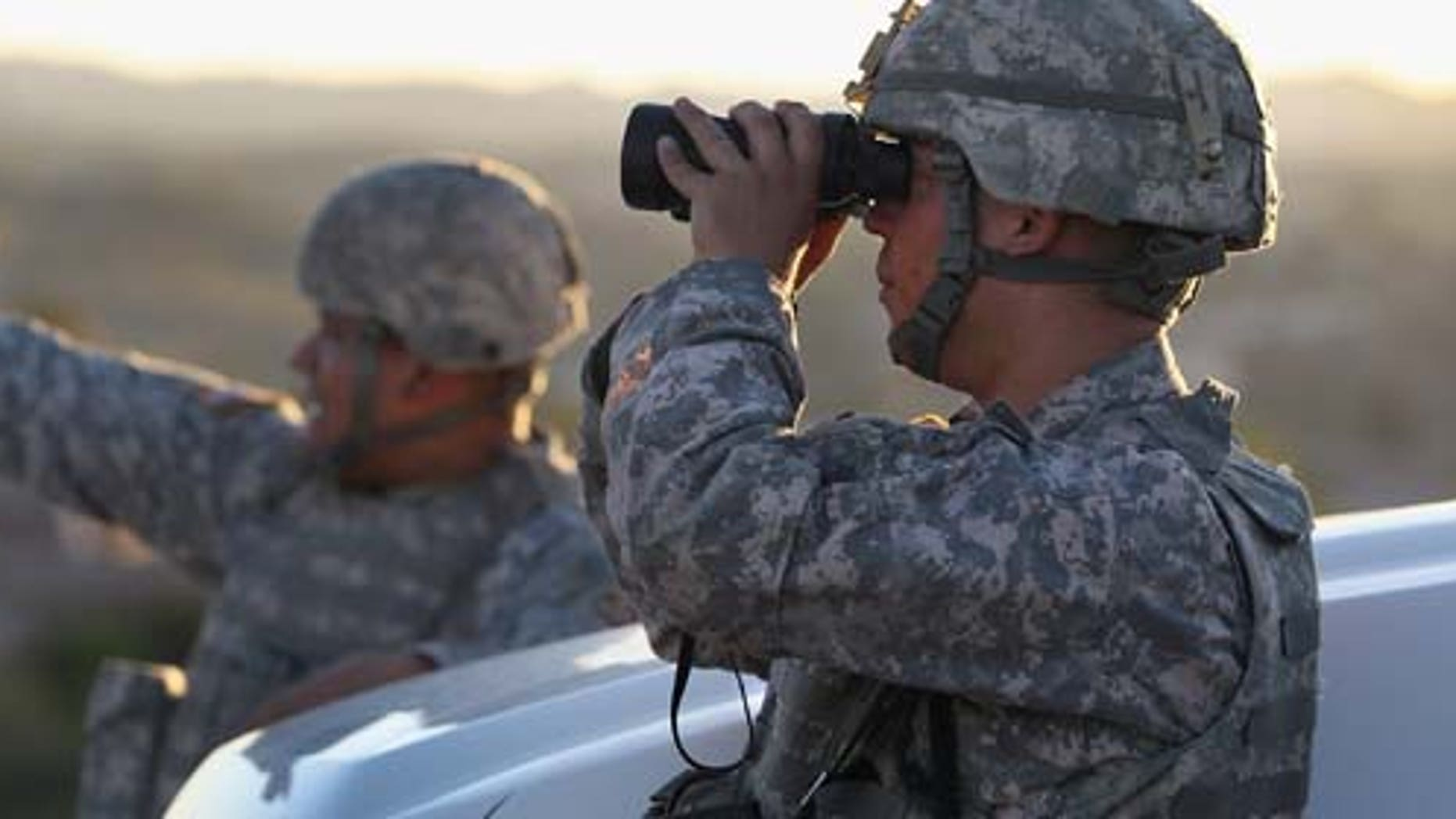 NOGALES, AZ - JUNE 22:  U.S. Army National Guardsmen scan the U.S.-Mexico border on June 22, 2011 in Nogales, Arizona. The Obama administration will reduce the number of troops along the Mexican border, a spokesman for a Texas congressman said on Dec. 13, 2011. (Photo by John Moore/Getty Images)