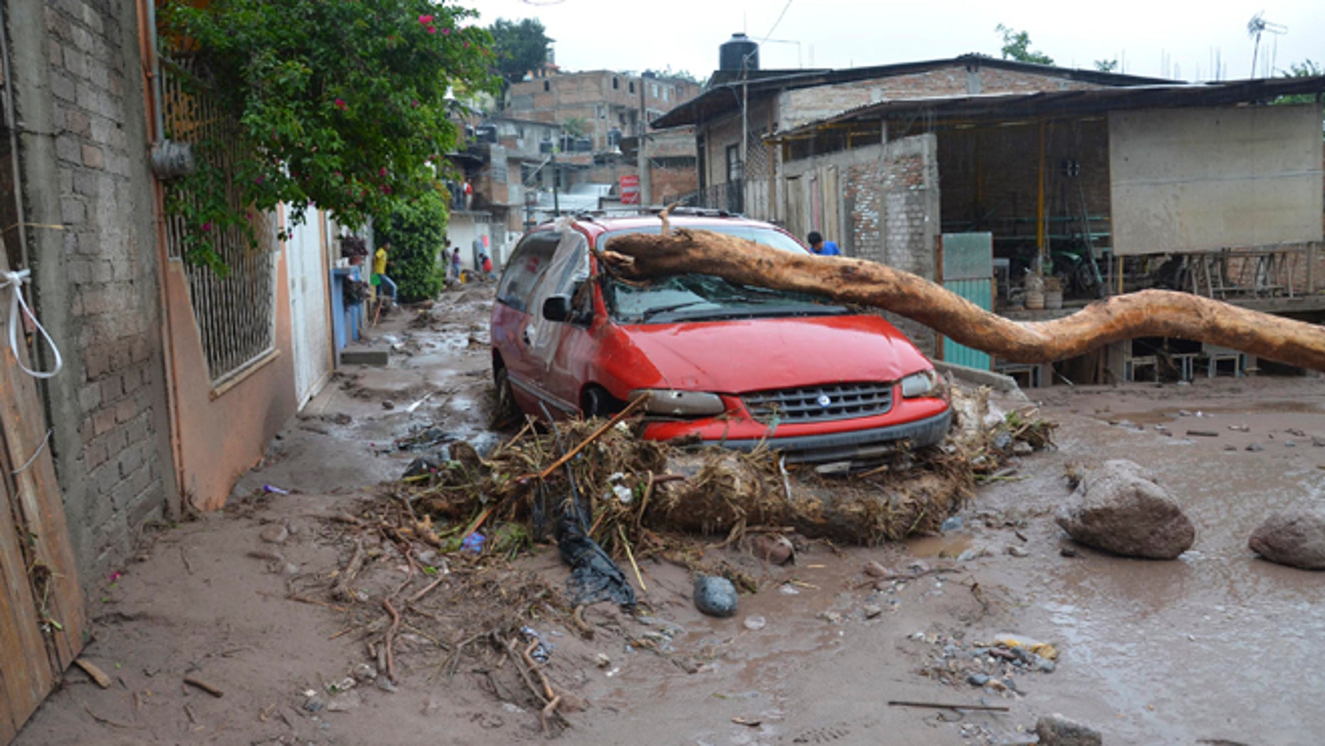A damaged vehicle stands in the middle of a road after a landslide caused by heavy rains came down on a low income neighborhood in the city of Chilpancingo, Mexico, Monday Sept. 16, 2013.  Tropical Storm Ingrid and remnants of Tropical Storm Manuel drench Mexico's Gulf and Pacific coasts, flooding towns and cities in a national emergency that federal authorities say has caused at least 34 deaths. (AP Photo/Alejandrino Gonzalez)