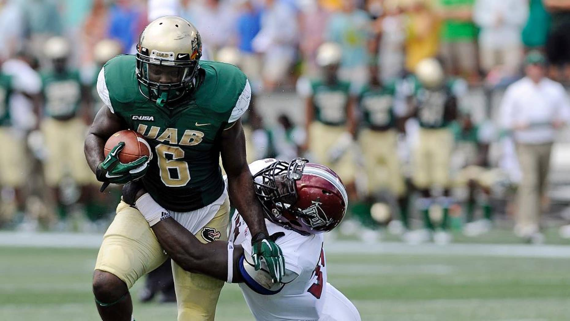 UAB running back D.J. Vinson (6) attempts to break away from Troy linebacker Mark Wilson (35) during the first half an NCAA college football in Birmingham, Ala.,  Saturday, Aug. 30, 2014. (AP Photo/The (Troy) Messenger, Thomas Graning)