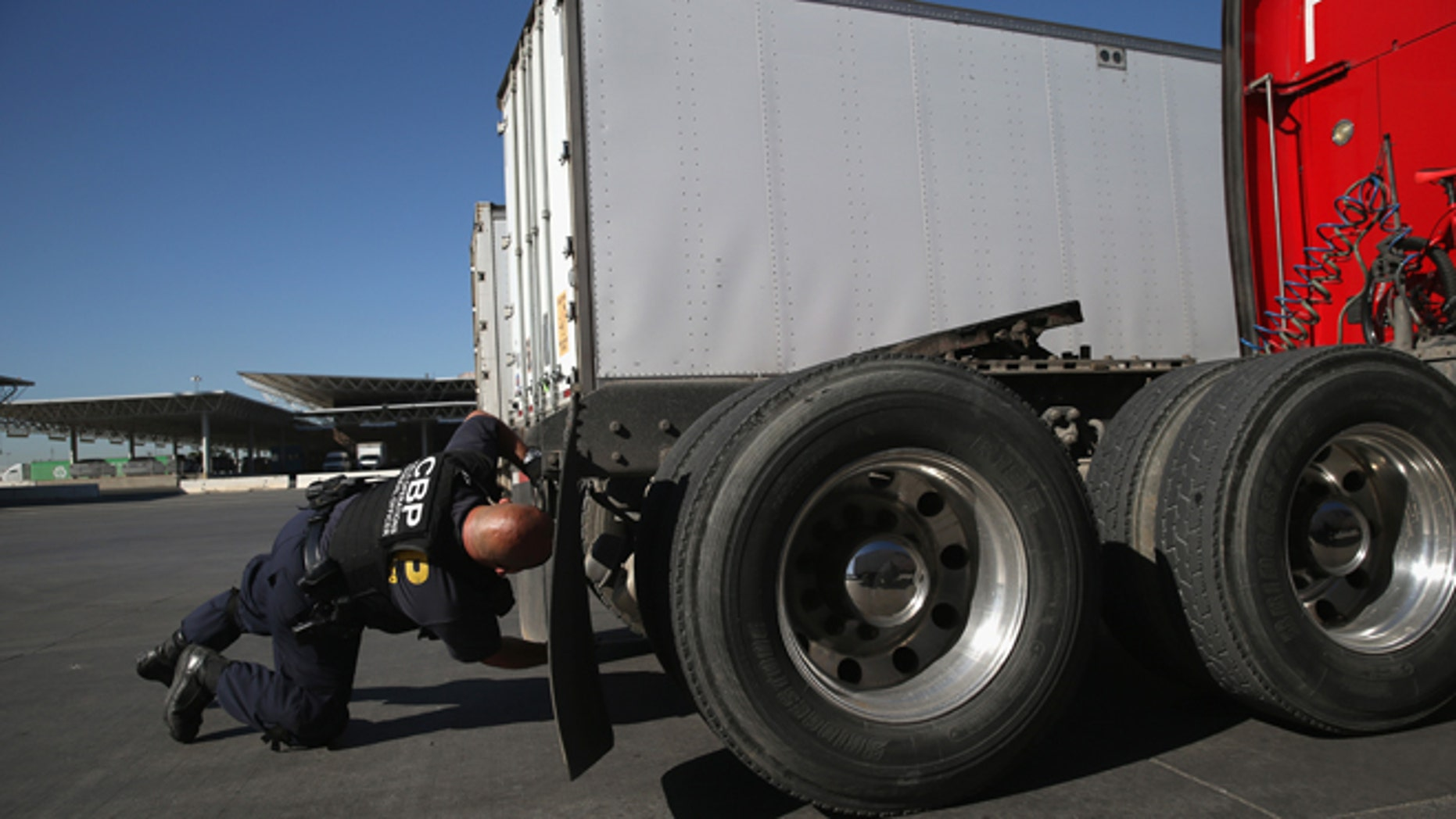 SAN DIEGO, CA - NOVEMBER 14:  A U.S. Customs and Border Protection inspects a truck coming from Mexico into the United States at the Otay Mesa port of entry on November 14, 2013 in San Diego, California. Otay Mesa is the second busiest cargo port in the southwestern United States, with some 750,000 trucks passing through annually. (Photo by John Moore/Getty Images)