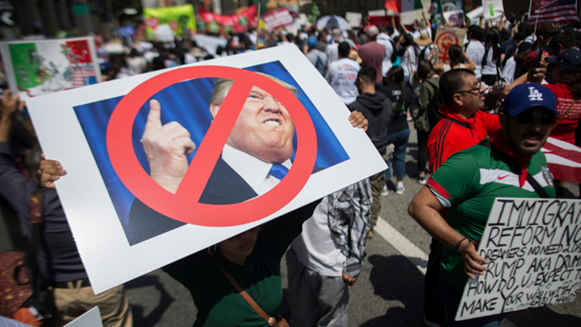 A woman carries a placard critical of Republican presidential candidate Donald Trump during one of several May Day marches on May 1, 2016 in Los Angeles, California.  (Photo by David McNew/Getty Images)