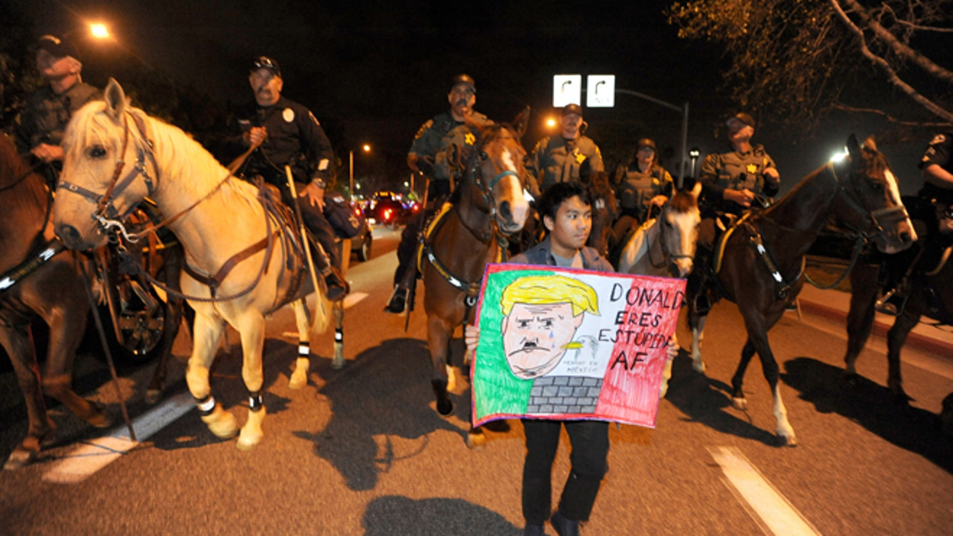 Police on horseback and on foot clear the anti-Trump demonstrators on Thursday, April 28, 2016, in Costa Mesa, Calif.