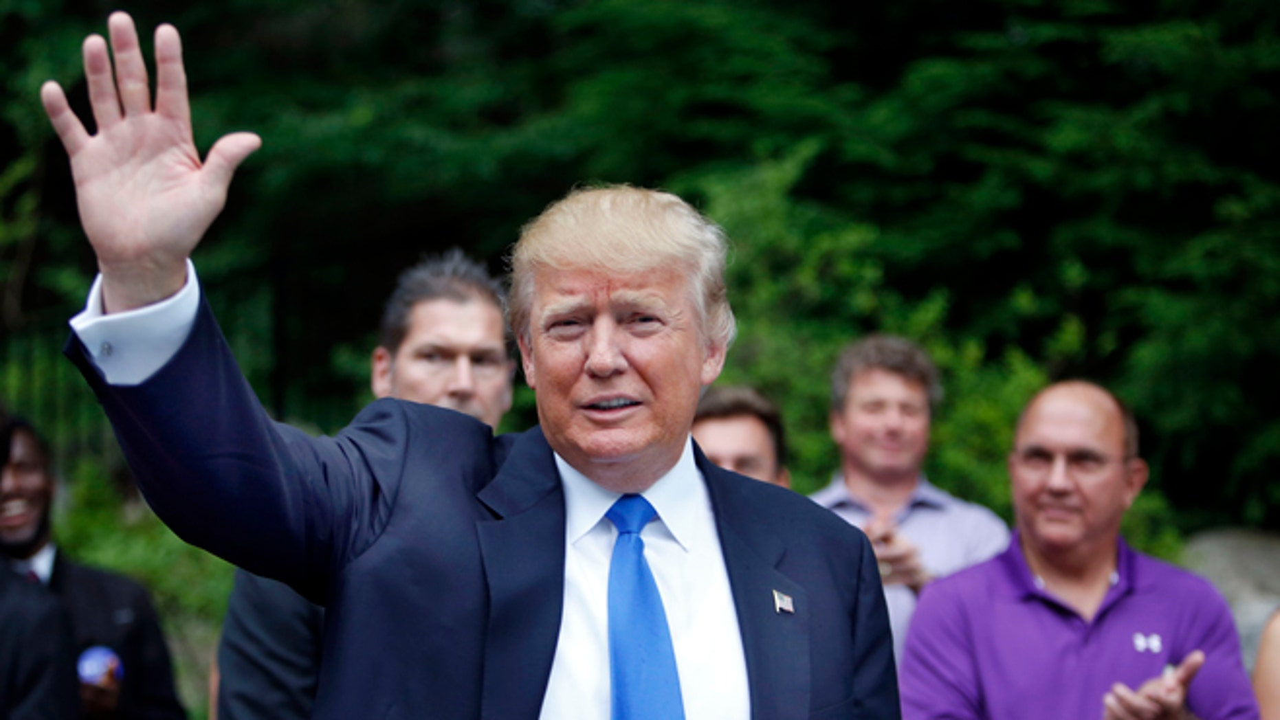 FILE - In this Tuesday, June 30, 2015 file photo, Republican presidential candidate Donald Trump waves as he arrives at a house party in Bedford, N.H. Alex Nogales, president of the National Hispanic Media Coalition, said Thursday, July 9, 2015, that more organizations need to follow the example of NBC and cut business ties with Trump.  (AP Photo/Jim Cole, File)