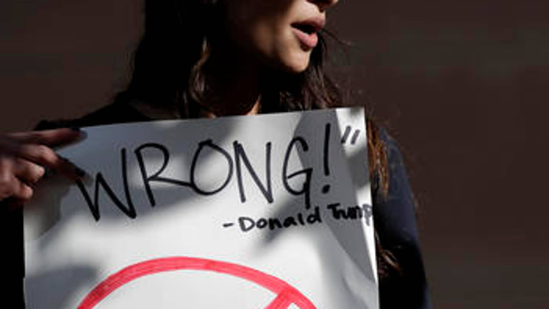 Senya Merchant holds a sign against President-elect Donald Trump's now-defunct Trump University Friday, Nov. 18, 2016, in San Diego. Trump agreed Friday to pay $25 million to settle several lawsuits alleging that his former school for real estate investors defrauded students who paid up to $35,000 to enroll in Trump University programs.(AP Photo/Gregory Bull)