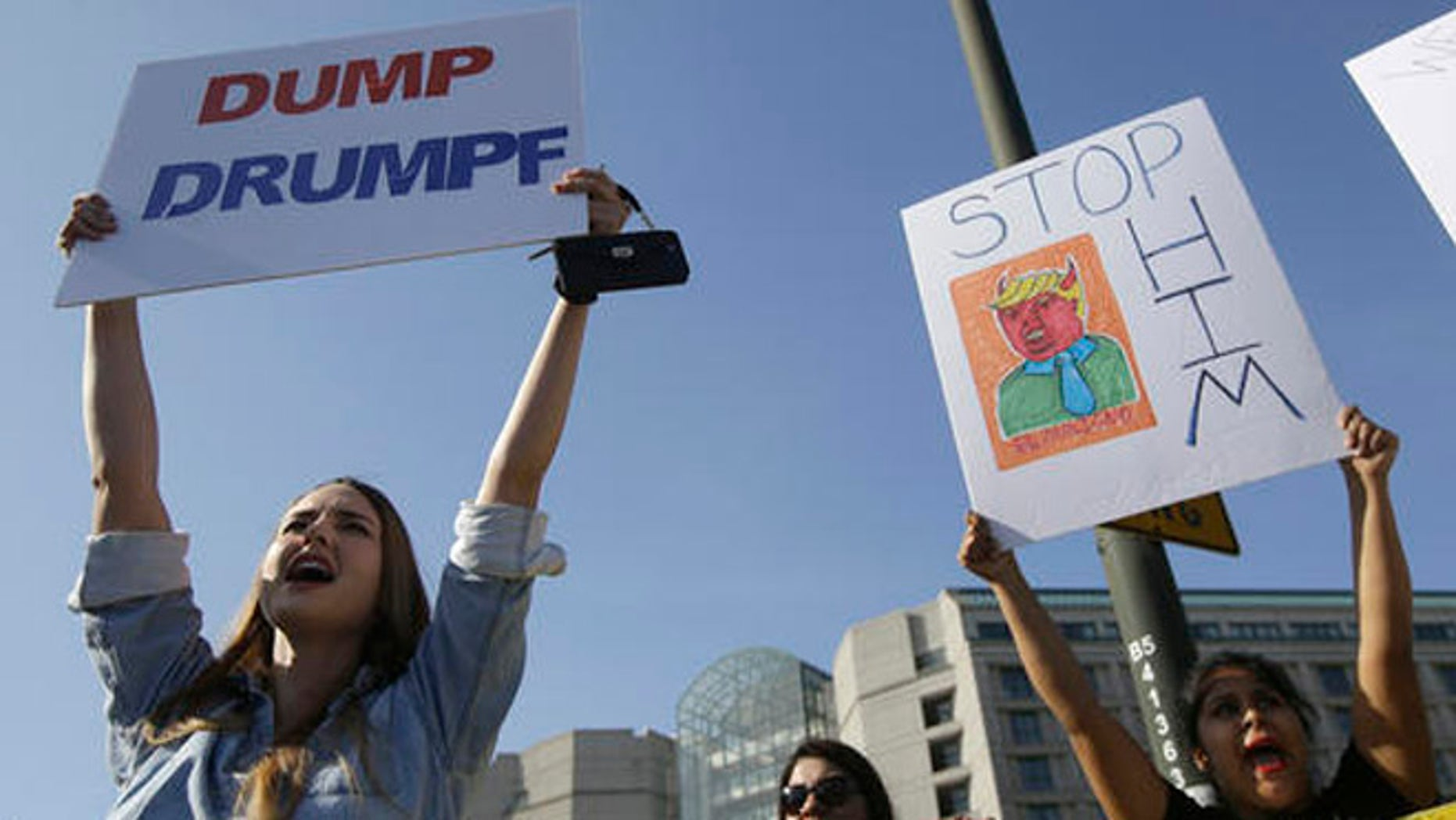 Women hold up signs protesting Donald Trump outside of the Hyatt Regency hotel before the California Republican Party 2016 Convention in Burlingame, Calif., Friday, April 29, 2016. (AP Photo/Jeff Chiu)