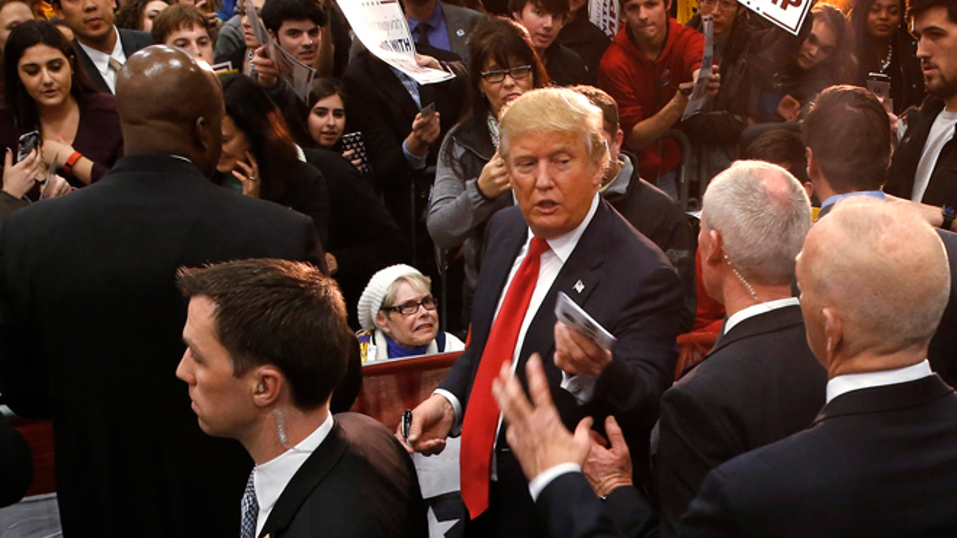 Republican presidential candidate Donald Trump hands a memento to staff during a campaign event at the University of Iowa Field House, Tuesday, Jan. 26, 2016 in Iowa City, Iowa. (AP Photo/Paul Sancya)