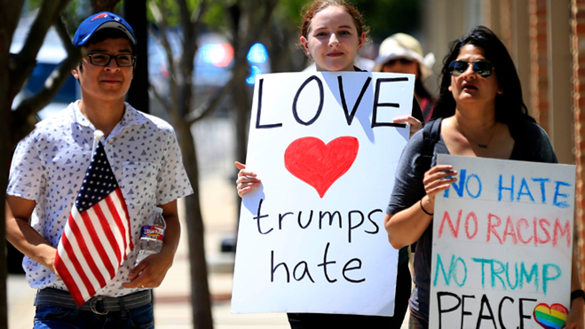 DALLAS, TX - JUNE 16: Protestors walk before Republican presidential candidate Donald Trump's rally on June 16, 2016 at Gilley's in Dallas, Texas. Trump arrived in Texas on Thursday with plans to hold rallies and fundraisers. (Photo by Ron Jenkins/Getty Images)