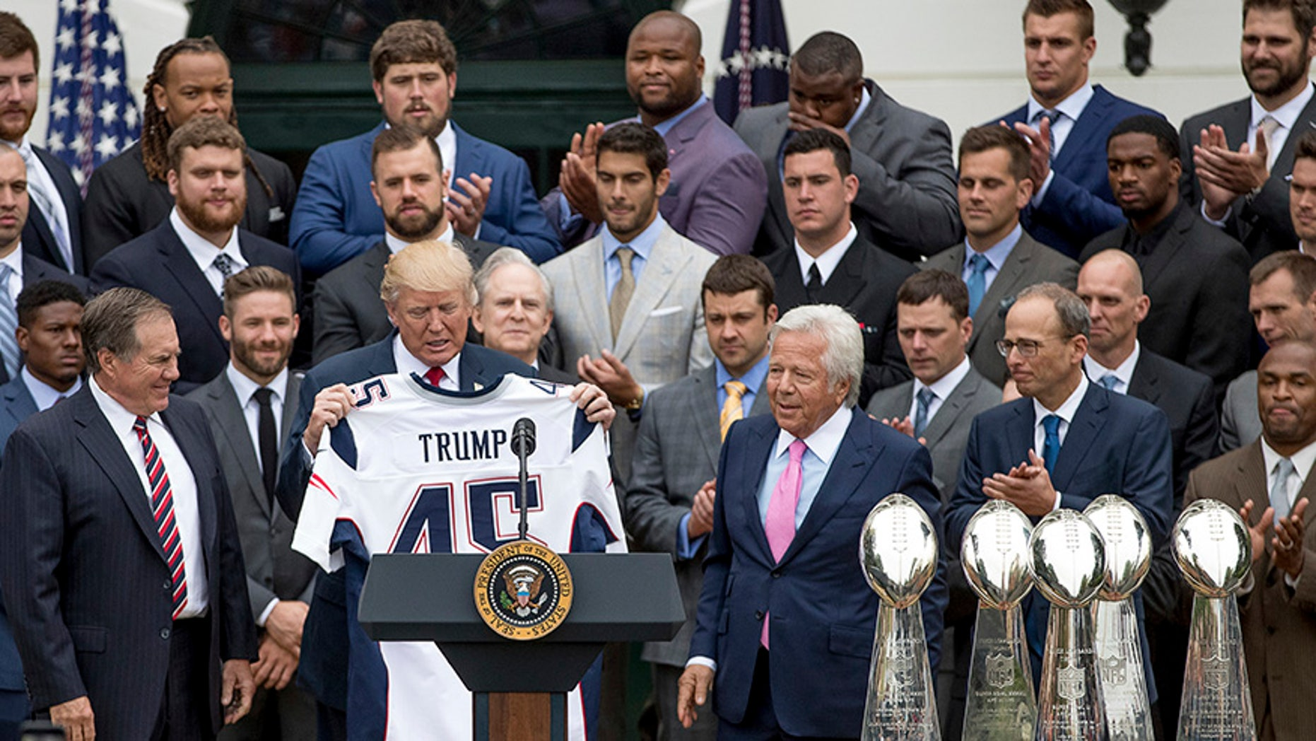 President Donald Trump is presented with a New England Patriots jersey by Patriots head coach Bill Belichick, left, and New England Patriots owner Robert Kraft, center, during a ceremony on the South Lawn of the White House in Washington, Wednesday, April 19, 2017, where the president honored the Super Bowl Champion New England Patriots for their Super Bowl LI victory. Also pictured is New England Patriots president Jonathan Kraft, second from right. (AP Photo/Andrew Harnik)