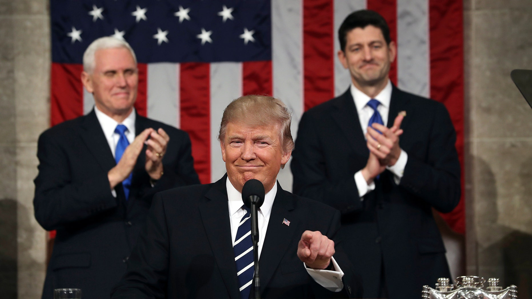 President Donald Trump, flanked by Vice President Mike Pence and House Speaker Paul Ryan of Wis., gestures on Capitol Hill in Washington, Tuesday, Feb. 28, 2017, before his address to a joint session of Congress. (Jim Lo Scalzo/Pool Image via AP)