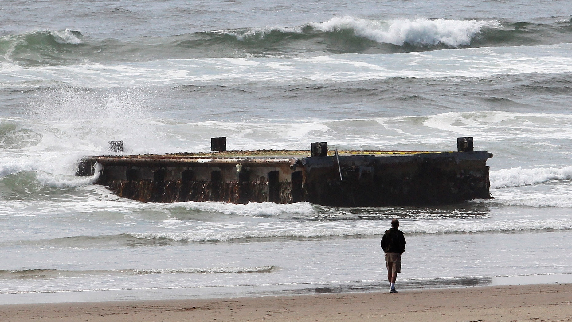 June 6, 2012: In this file photo, a man looks at a 70-foot-long dock with Japanese lettering that washed ashore on Agate Beach in Newport, Ore.