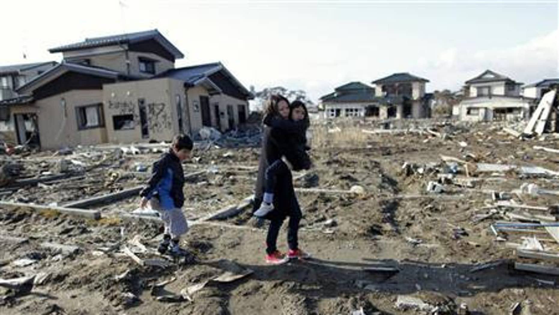 Wakana Kumagai, 7, carried by her mother Yoshiko and followed by her brother Koki visit the spot where their house, which was washed away by the March 11, 2011 tsunami, used to stand in Higashimatsushima, Miyagi prefecture