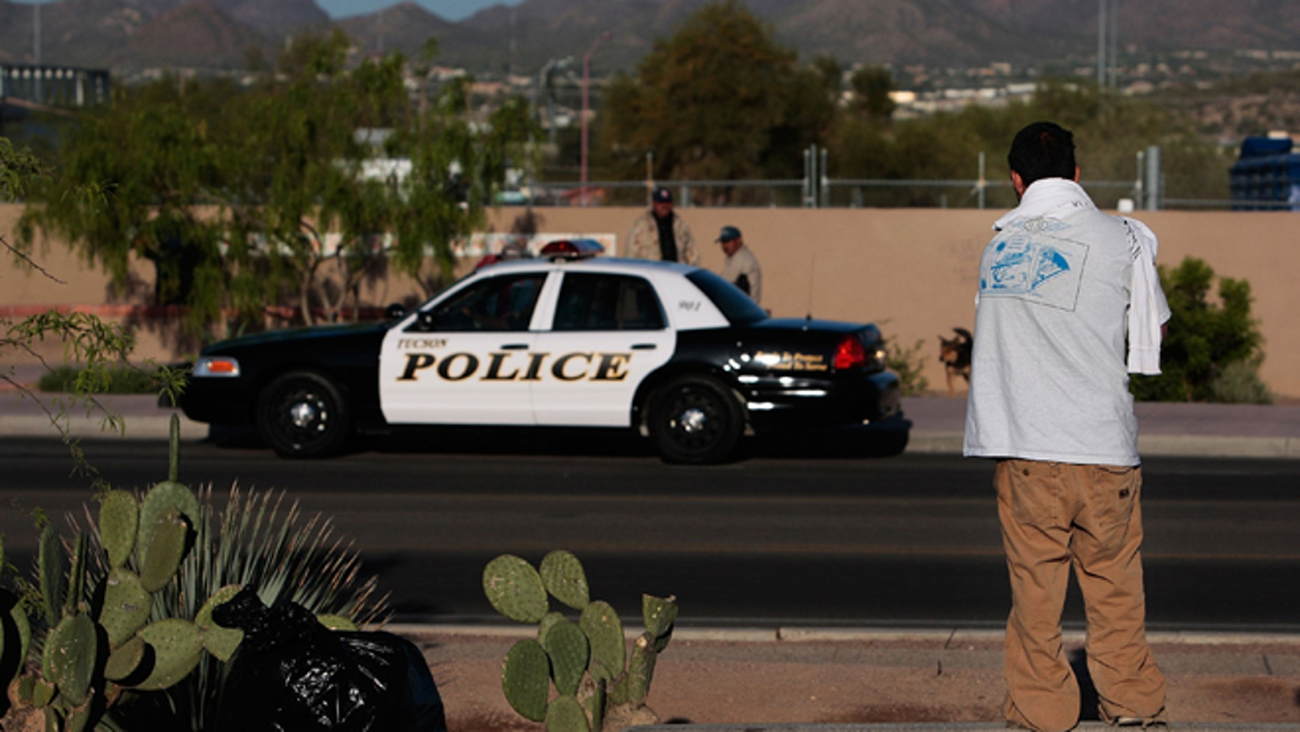 A Hispanic day laborer looking for work watches a police car parked across the street April 5, 2008 in Tucson, Arizona. (Photo by Chris Hondros/Getty Images)