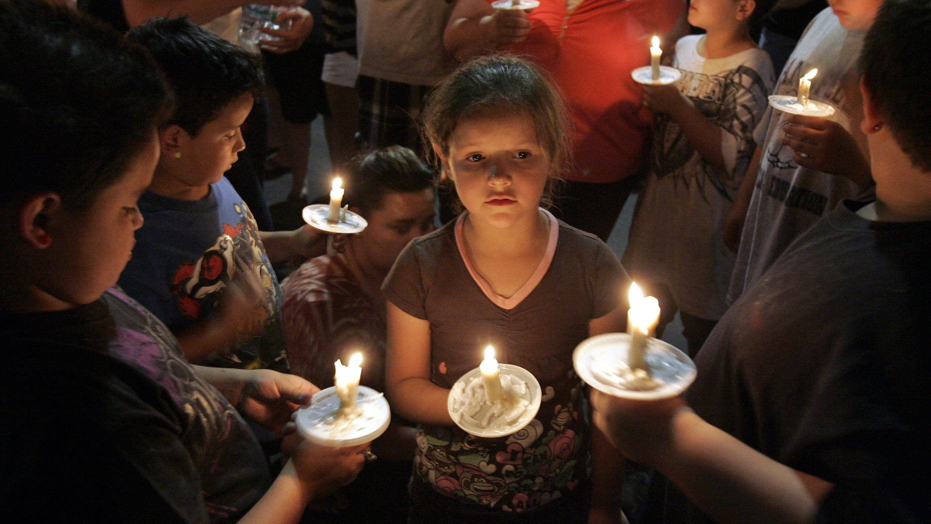 April 22: Children with their parents light and hold candles at a vigil in the parking lot near a police command post in Tucson, Ariz., in honor of the missing 6-year-old Isabel Celis.