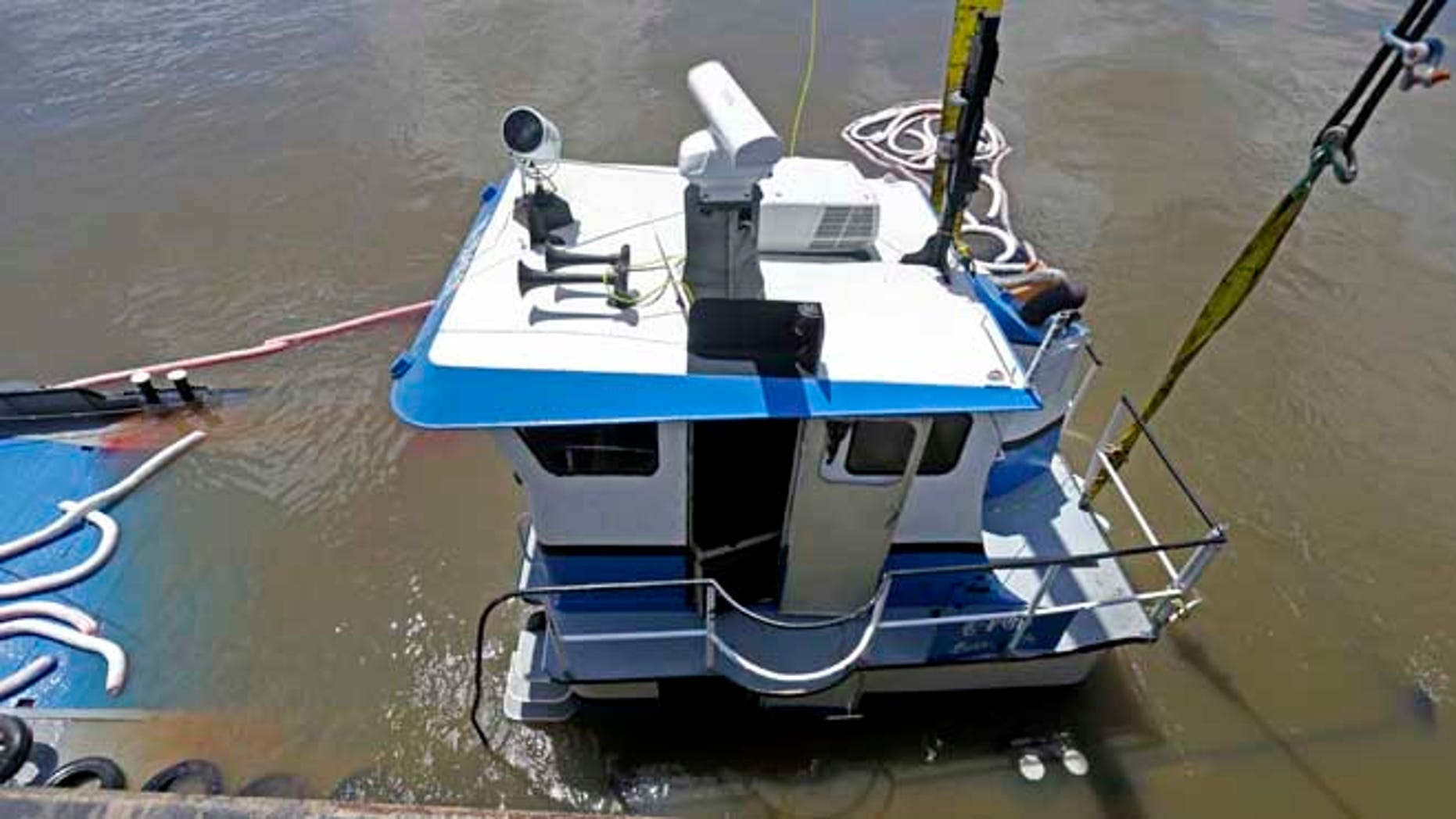 """July 10, 2013: Workers raise """"C-Pec,"""" the 47 foot tugboat which sank Saturday in the middle of the Mississippi River, near Venice, La."""
