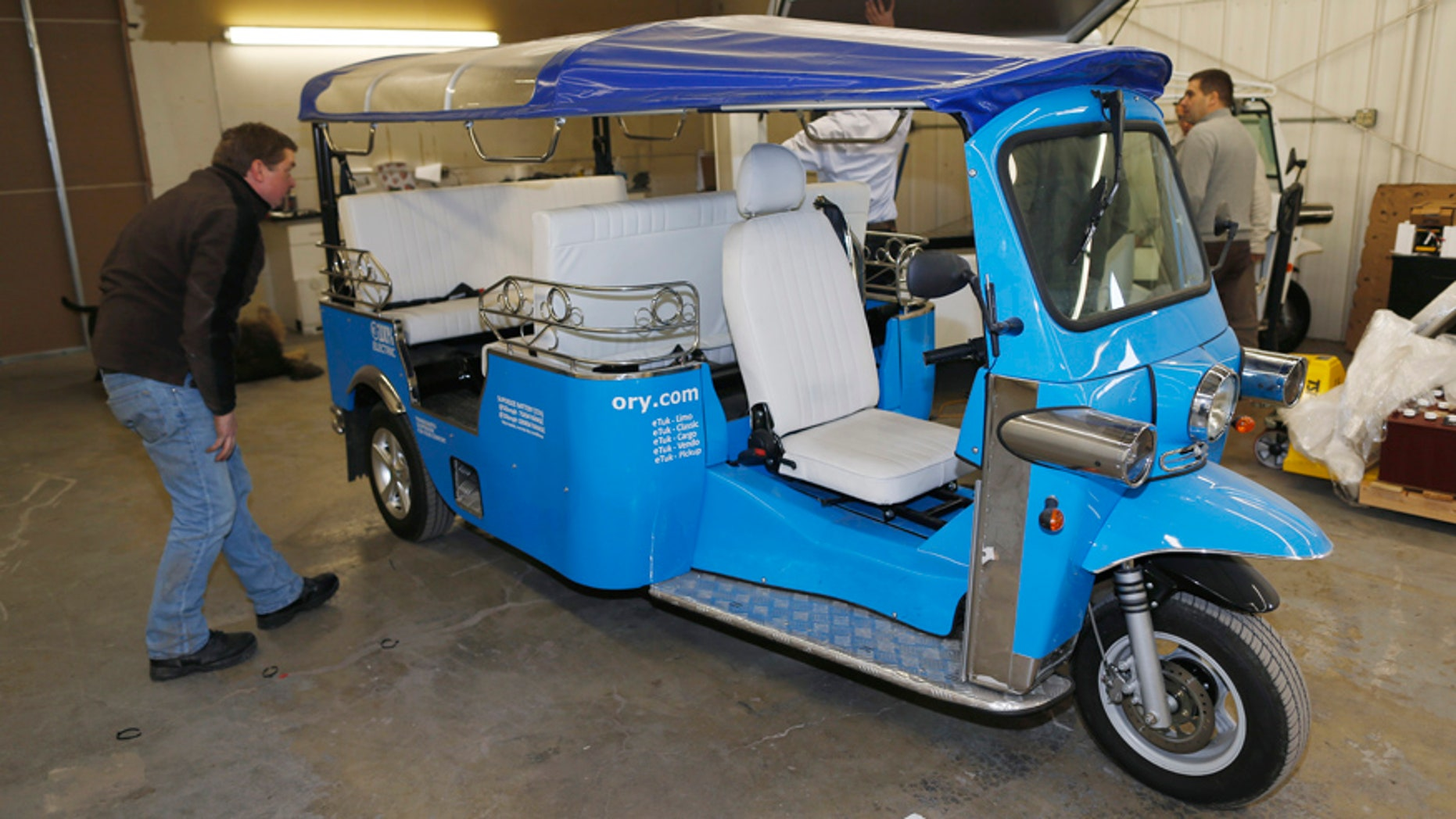 In this photo taken Friday, Feb. 27, 2015, a worker checks the roof on an electric Tuk-Tuk being prepared for export at the Denver eTuk factory in northeast Denver. The Tuk Tuk Factory, based in Amsterdam, has signed a licensing agreement with Denver-based eTuk USA to allow the company to manufacture and sell an electric version of the vehicle. The companys founders hope the eco-friendly vehicles, a far cry from the loud, pollution-spewing versions common in Asia and South America, will become the next hip mode of transportation for urban dwellers and tourists across the country. (AP Photo/David Zalubowski)