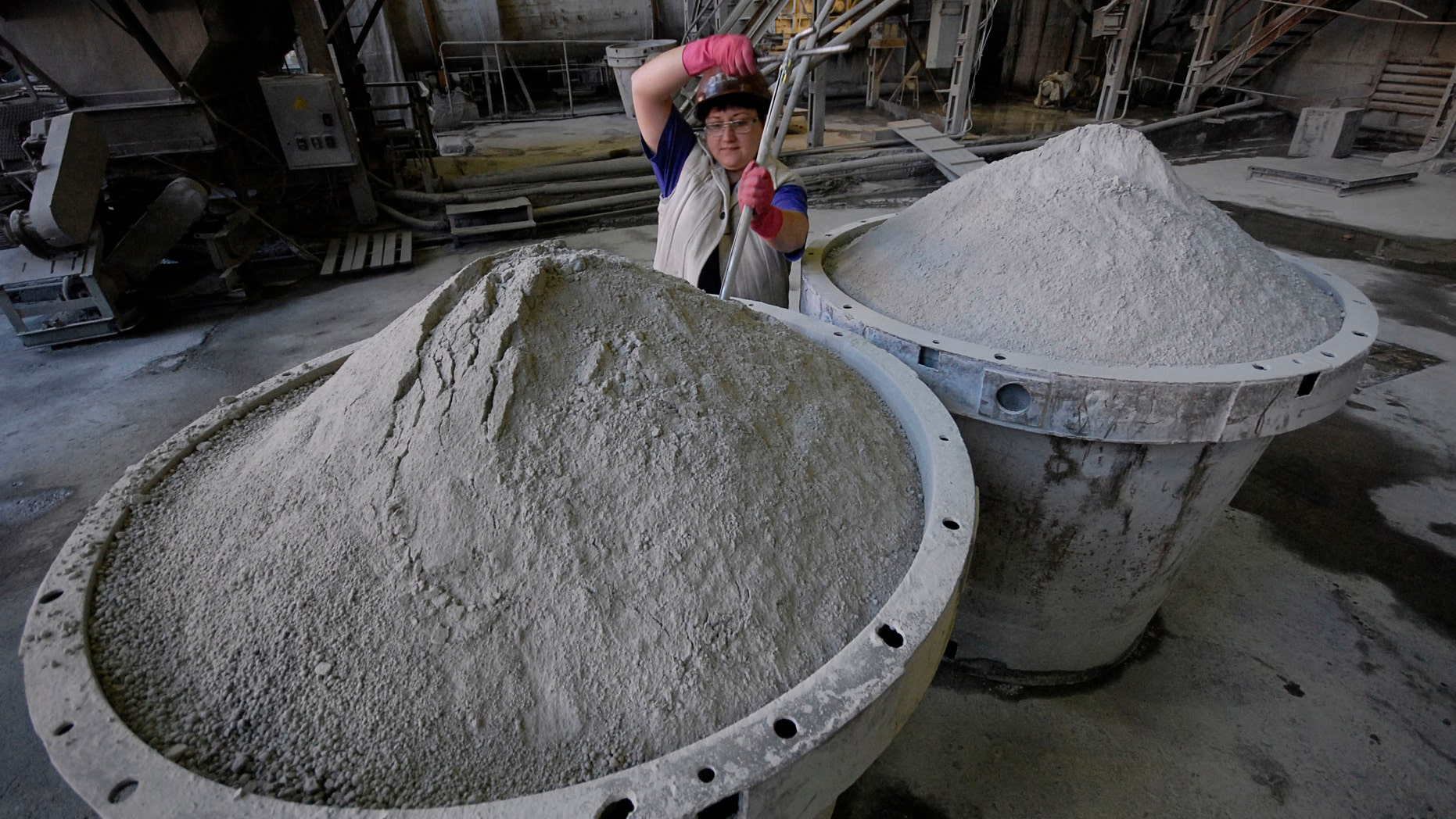 An employee controls the quality of tungsten concentrate at an ore-dressing mill at a Taiga settlement Vostok.