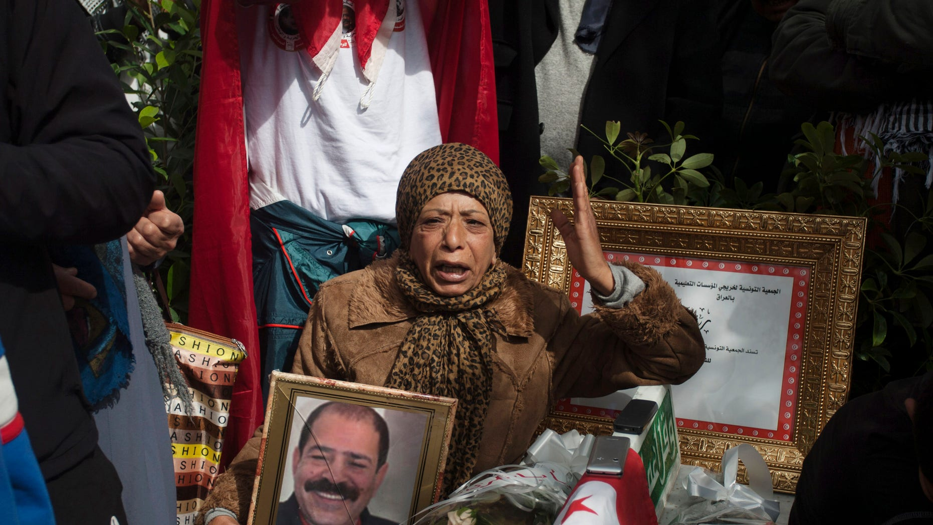 A protestor holds a portrait of slain Tunisian opposition leader Chokri Belaid, during a demonstration to mark 40 days since his death, in Tunis, Saturday, March 16, 2013. (AP Photo/Amine Landoulsi)
