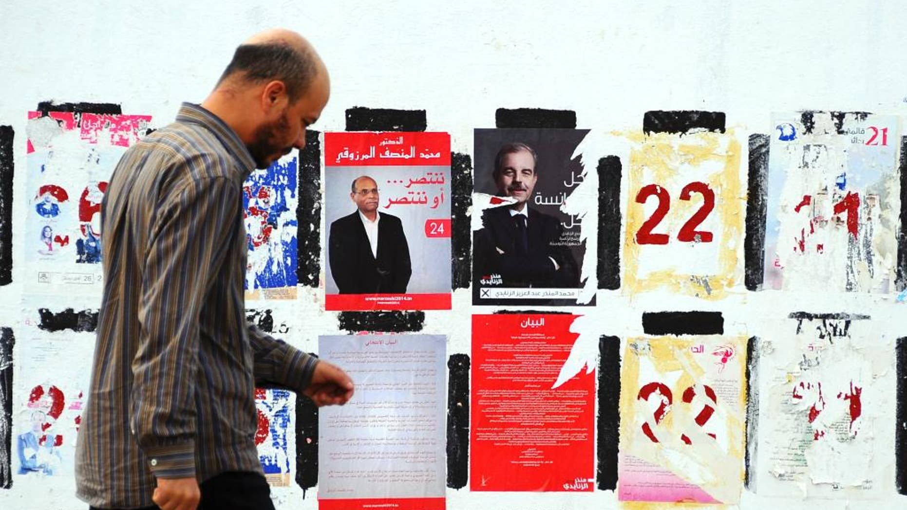 In this photo taken Wednesday, Nov. 5, 2014, a man walks past electoral posters for the upcoming presidential elections in Tunis. Campaign posters and banners for next week's presidential elections have covered the walls of Tunisia's cities and towns, papering over the flaking posters from the parliamentary elections just three weeks ago. (AP Photo/Hassene Dridi)