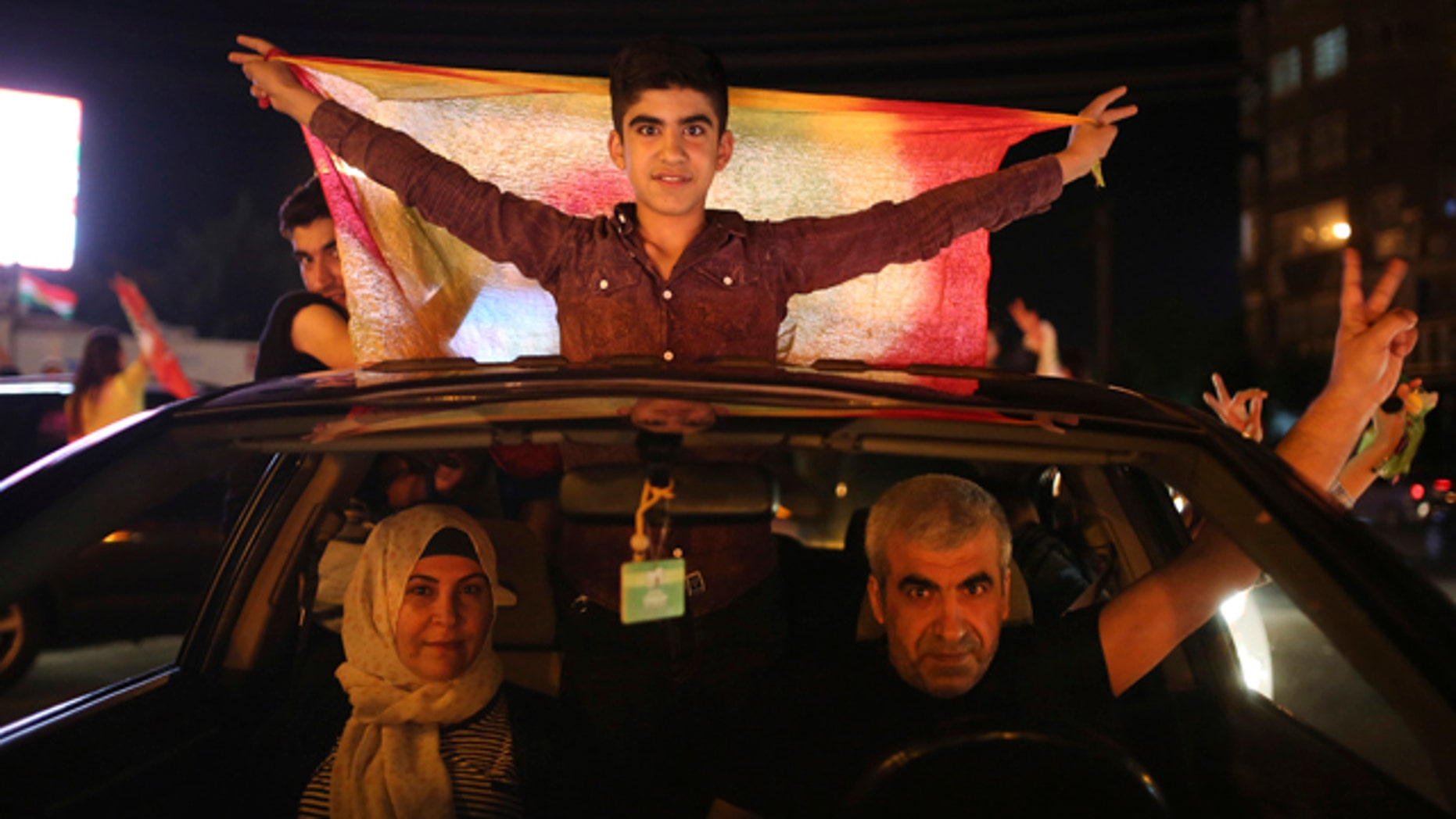 June 7, 2015: Supporters of the pro-Kurdish Peoples' Democratic Party (HDP) celebrate in Diyarbakir, southeastern Turkey. In a stunning rebuke of President Recep Tayyip Erdogan's ambitions to expand his powers, Turkish voters stripped his party of its simple majority in parliament, preliminary election results showed Sunday. (AP Photo/Emrah Tazegul)