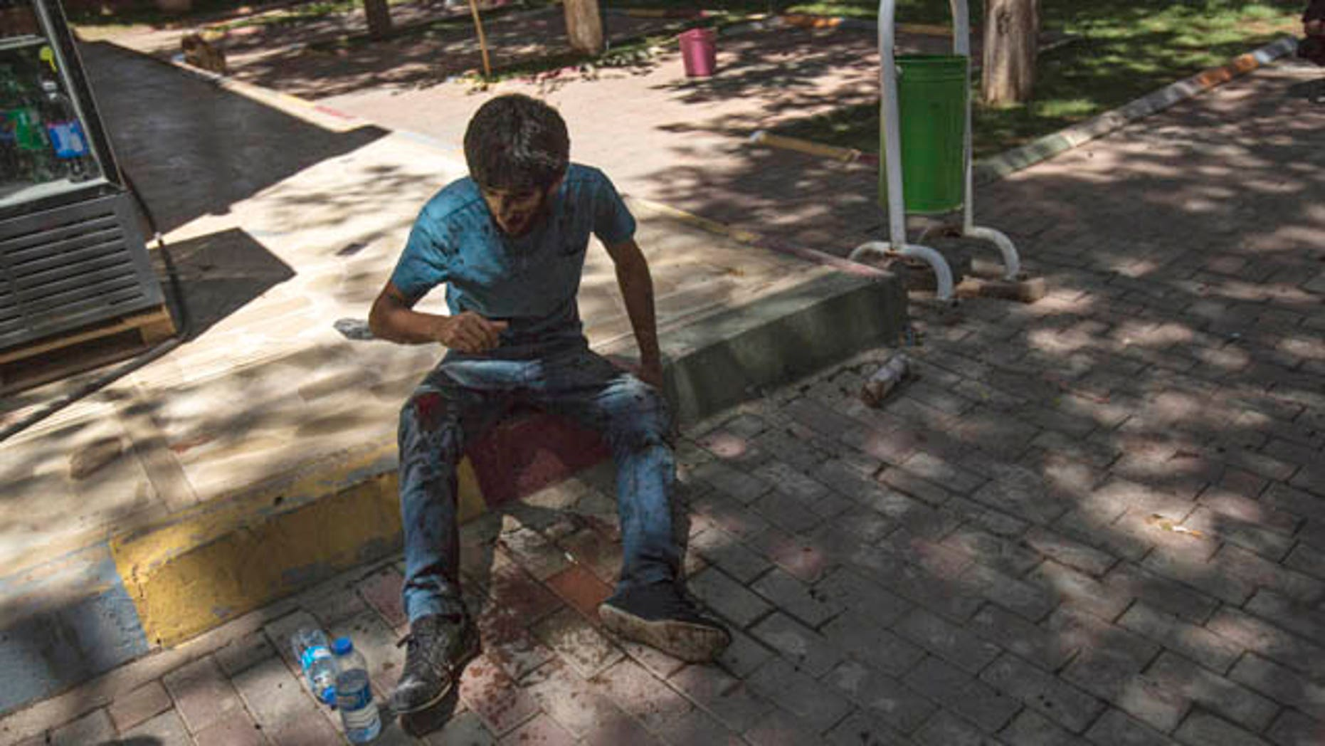 July 20, 2015: A youth wounded in an explosion that killed dozens of people and injured scores of others sits in the Turkish town of Suruc near the Syrian border (AP Photo/Zeki Yavuzak)