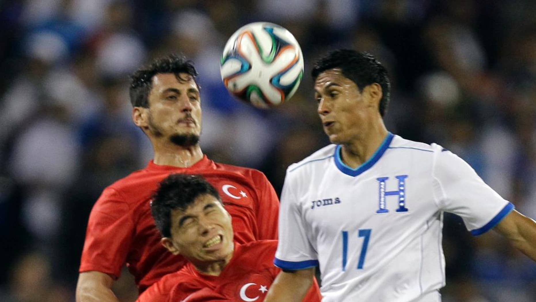 Turkey's Mustafa Pektemek, background, and Ishak Dogan (3) go up for the ball as Honduras' Andy Najar (17) defends during the first half of an exhibition soccer game, Thursday, May 29, 2014, in Washington. (AP Photo/Luis M. Alvarez)