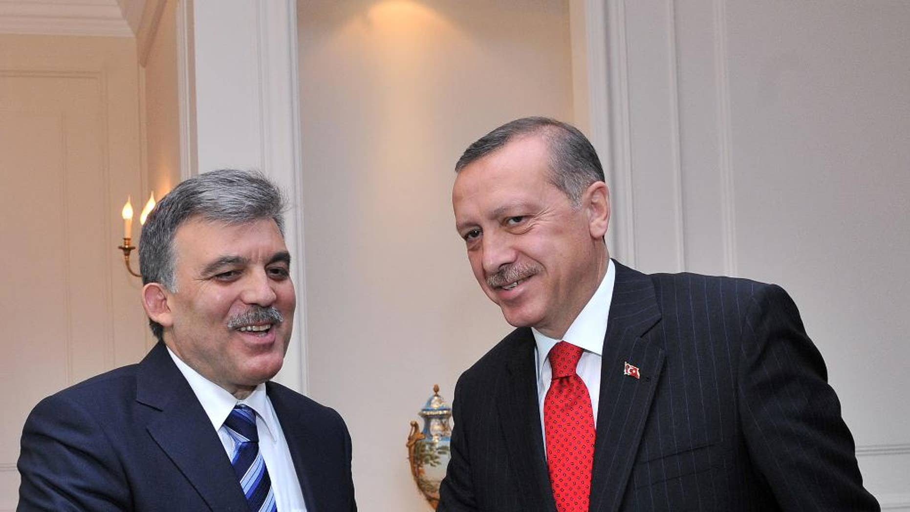 FILE - In this Tuesday, June 14, 2011 photo released by the Turkish Presidency Press Service, President Abdullah Gul, left, welcomes Prime Minister Recep Tayyip Erdogan in Ankara, Turkey. Turkish President Abdullah Gul has signaled that he doesn't want to swap jobs with Prime Minister Recep Tayyip Erdogan when the presidential term ends later this year. Gul said Friday he opposes a model similar to that of Russia where the president and prime minister have traded places and one has ruled in the other's shadow. Gul suggested he would not oppose Erdogan if he chose to run for president in the election in August. Erdogan has not made a decision about whether he will seek to become president _ a position that is largely ceremonial but does include the power to appoint the prime minister. He has said he wants a presidency with more executive powers. (AP Photo/Murat Cetinmuhurdar, Turkish Presidency Press Service, HO, file)