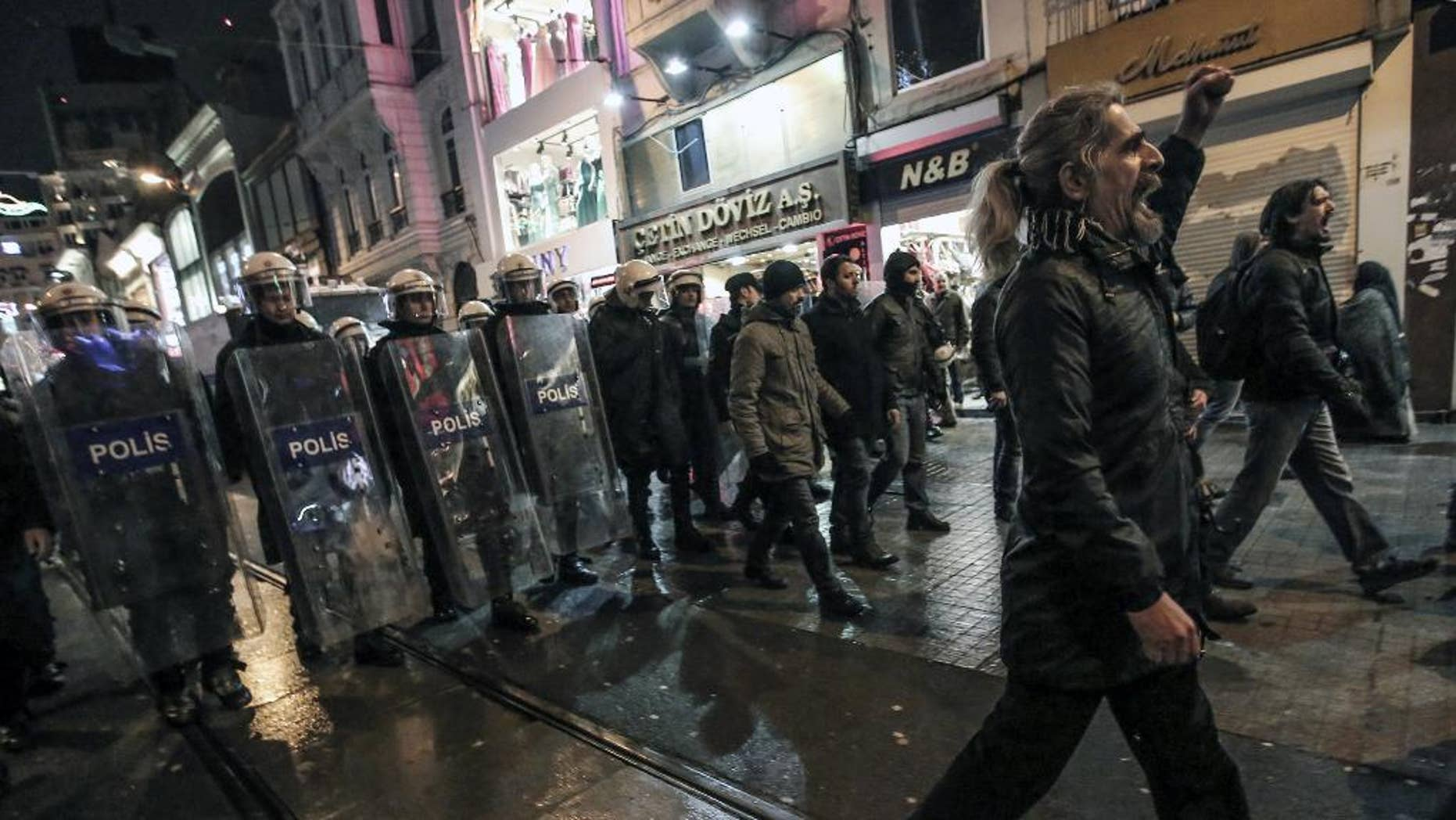People protest the death of Berkin Elvan, a Turkish teenager who was in a coma since being hit in the head by a tear gas canister fired by police during the summer's anti-government protests, in Istanbul, Turkey, Tuesday, March 11, 2014. The 15-year old Berkin Elvan's death in an Istanbul hospital _ nine months after he fell into a coma _ looked likely to spark new protests in Turkey. Riot police fired tear gas, water cannon and rubber bullets to disperse anti-government protesters trying to converge in central Ankara and Istanbul hours after Berkin Elvan's family announced his death.(AP Photo/Emrah Gurel)