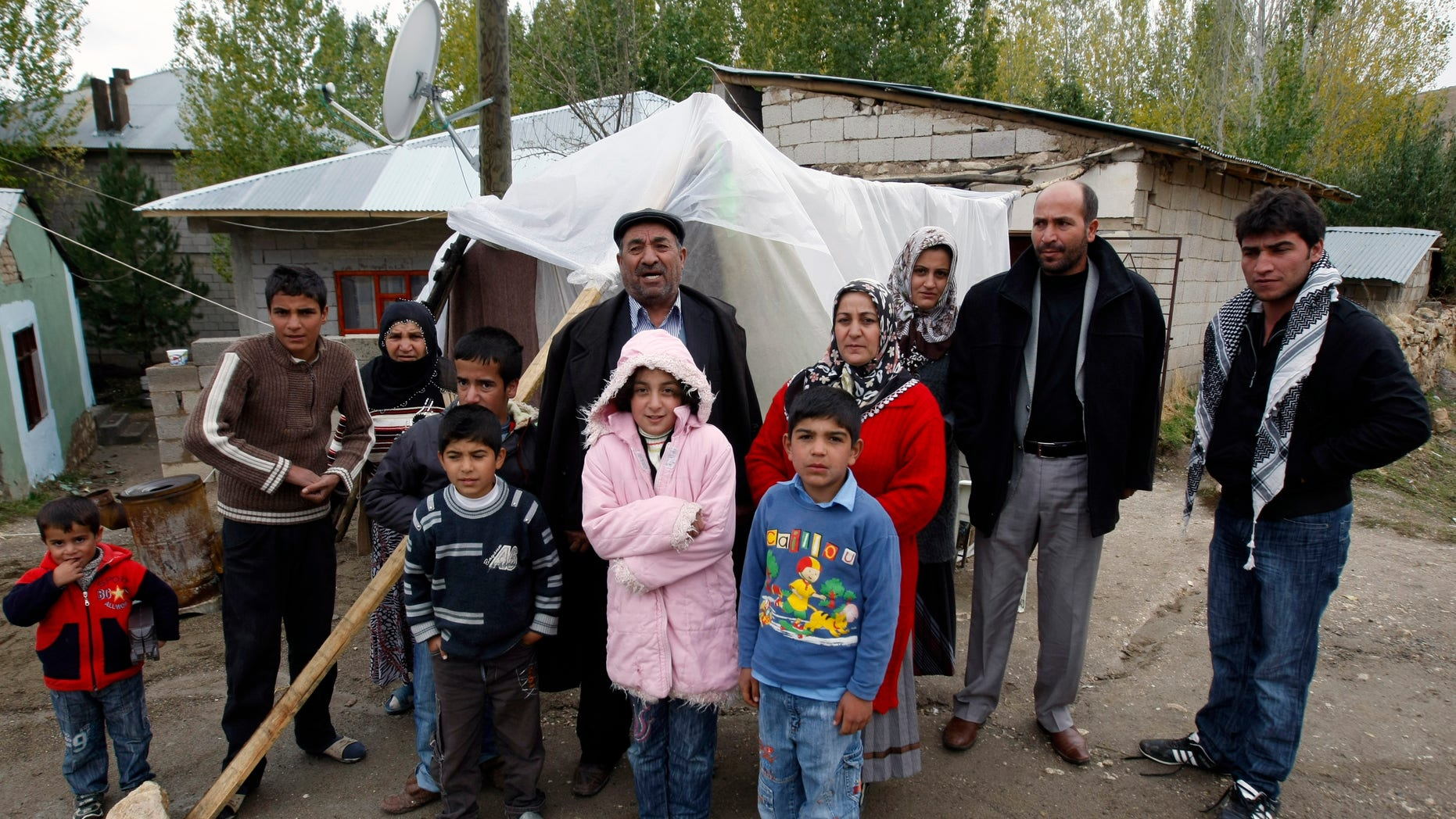 Oct. 27, 2011: Earthquake survivor, Adil Aktas, rear center, 56, and his family members stand outside their makeshift tent where about 10 people spent the night without any heating in a tent city set up in a soccer field in Ercis, Van, Turkey.