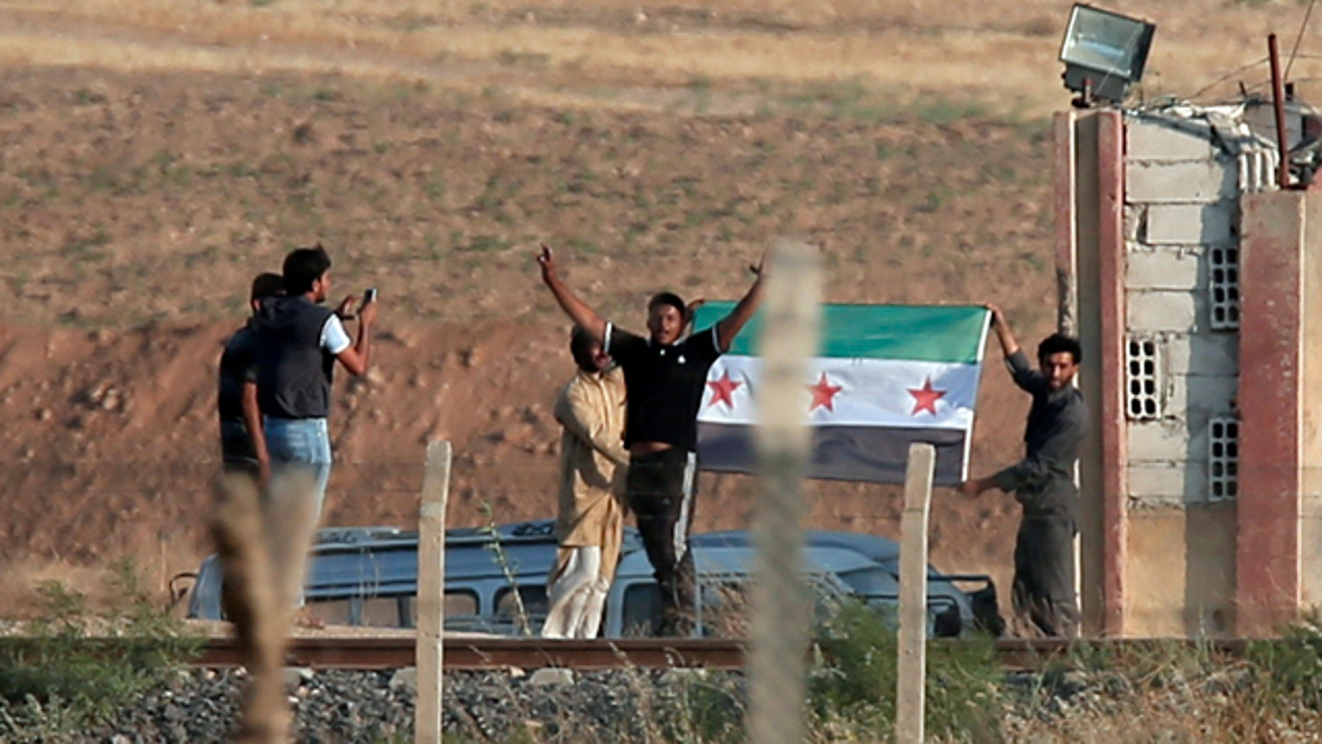 June 15, 2015: In this photo taken from the Turkish side of the border between Turkey and Syria, in Akcakale, southeastern Turkey, Kurdish people wave a Free Syria Army group flag in the outskirts of Tal Abyad, Syria. (AP Photo/Lefteris Pitarakis)