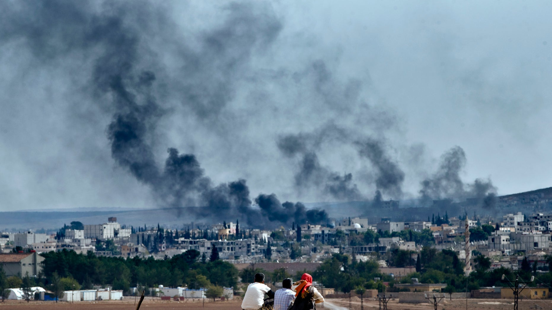 """Oct. 26, 2014 - Syrian Kurdish refugees from Kobani watch fighting across the border in Kobani from the outskirts of Suruc, Turkey, near the Turkey-Syria border. A new UN report says the world is facing a challenge of foreign fighters in terror groups on an """"unprecedented scale,"""" with about 15,000 in Syria and Iraq alone."""