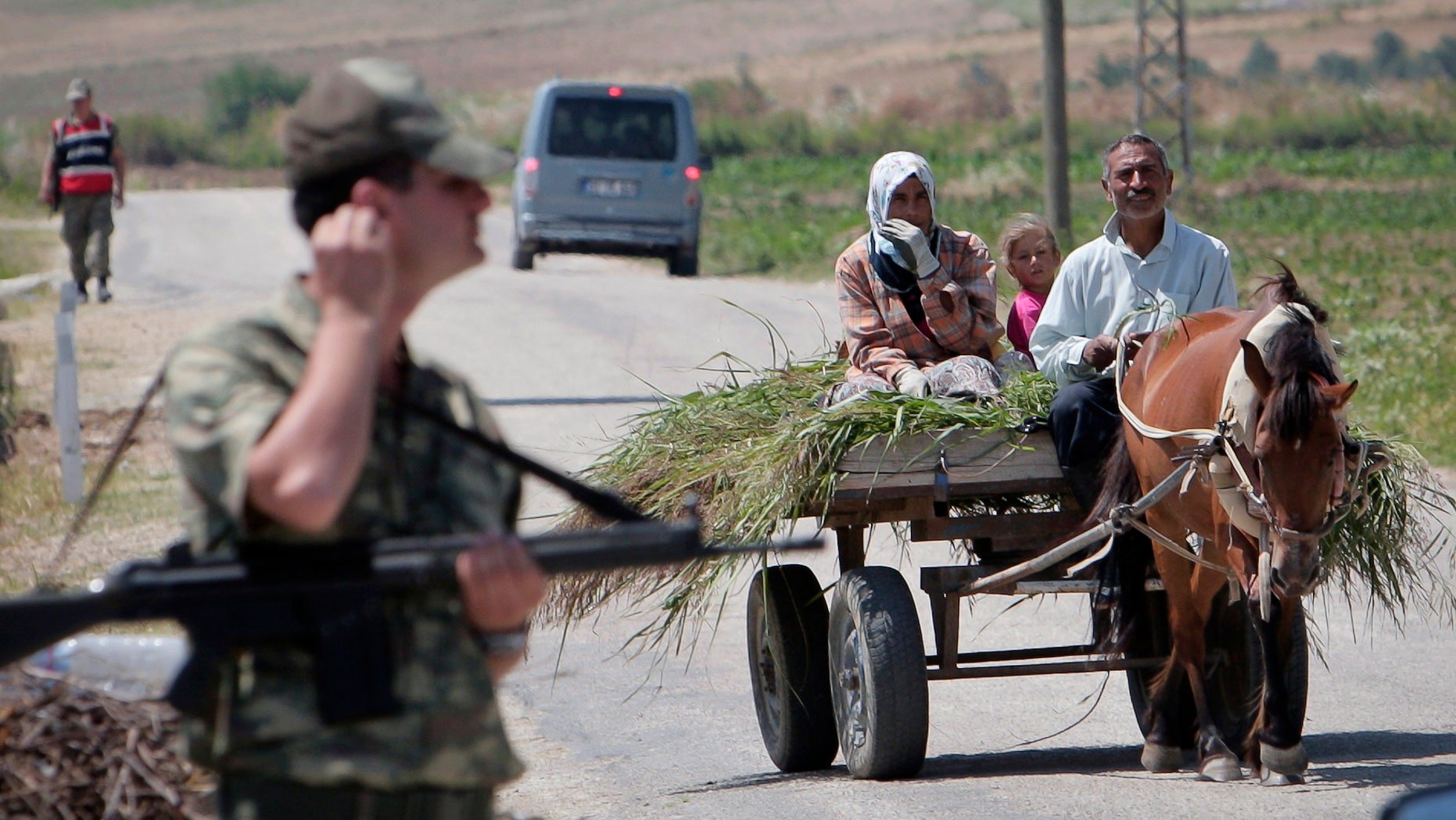 A Turkish family rides on a cart near Turkish soldiers guarding a Syrian refugee a camp, during a brief visit organized by Turkish authorities for the media, in Boynuyogun, Turkey, Saturday, June 18, 2011. According to Turkish authorities more than 10,000 Syrians are now in refugee camps in the Hatay province, near Turkey's border with Syria.