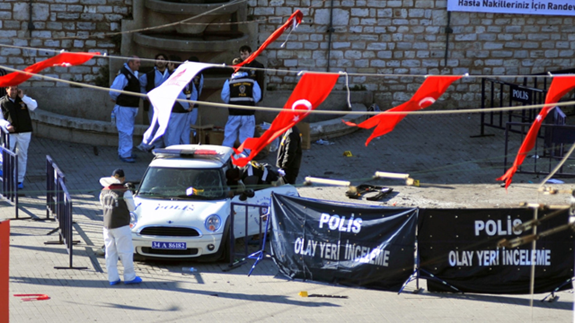 Police forensic officers inspect the scene after an explosion in Taksim square where riot police were stationed in case of demonstrations in Istanbul, Turkey, Sunday, Oct. 31, 2010. A suspected suicide bomber detonated a device in Istanbul's main square on Sunday, wounding 32 people, Istanbul's police chief said.