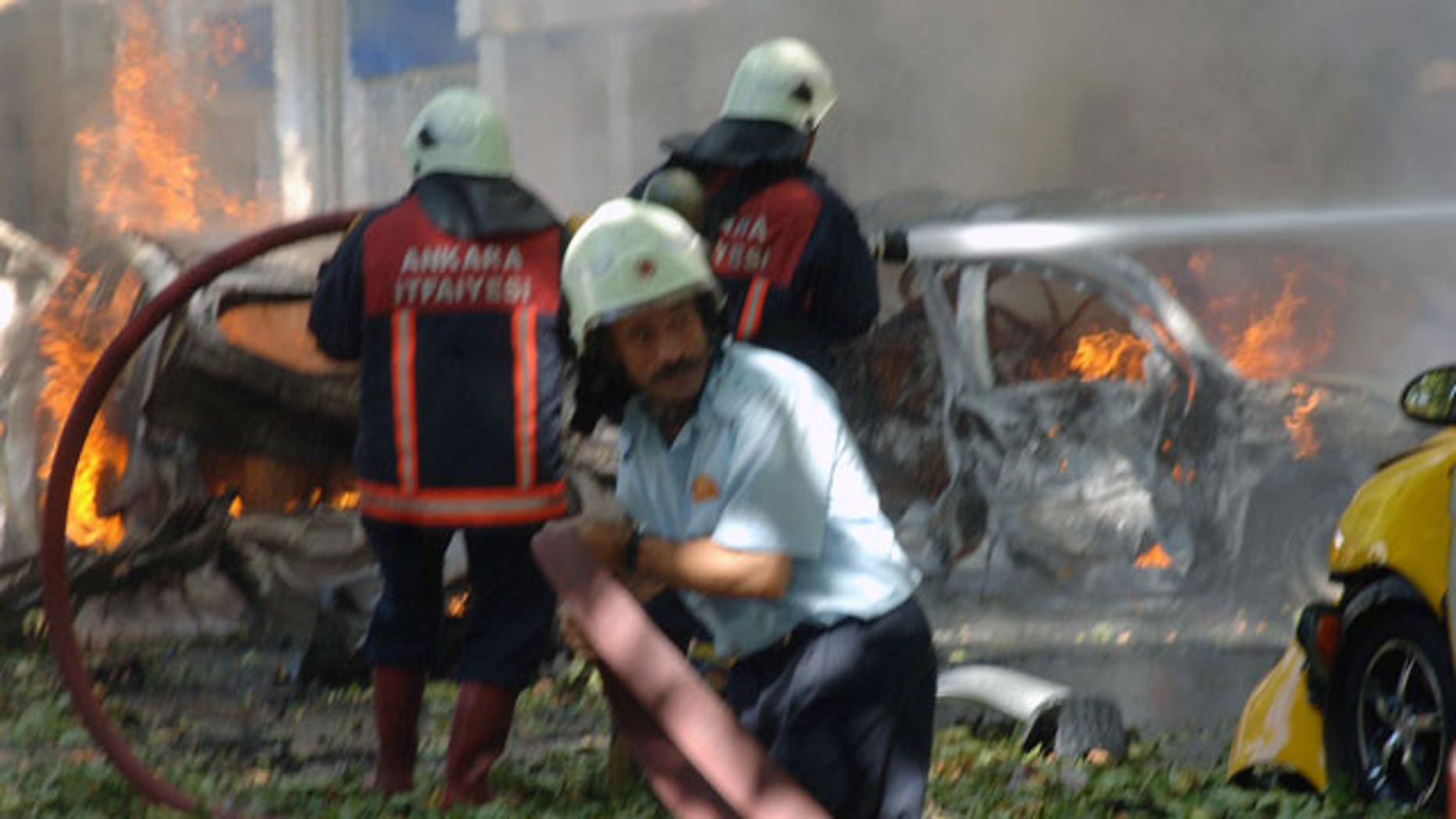 Firefighters are seen working at the site after a suspected car bomb exploded in a busy street in the Turkish capital Ankara, Turkey, Tuesday, Sept. 20, 2011.