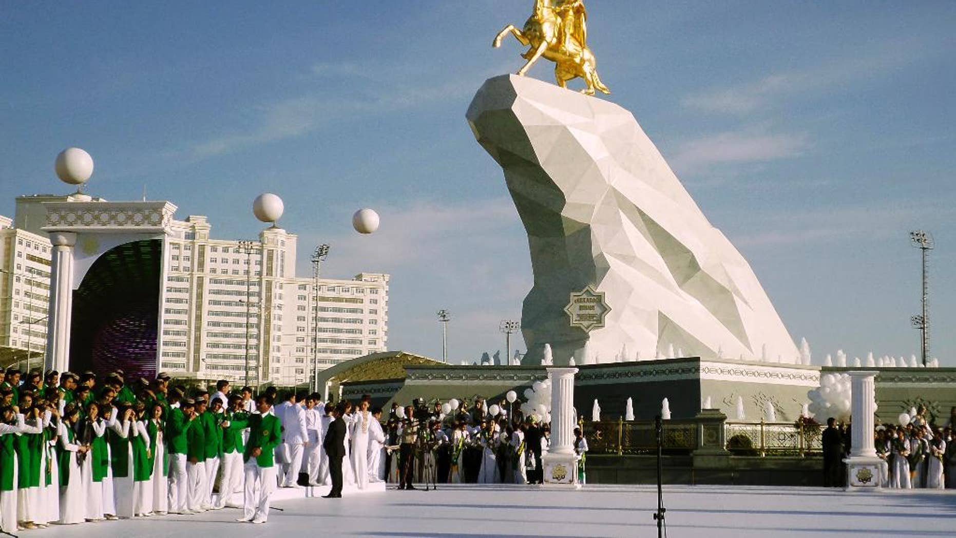People gather for the monument unveiling ceremony in Ashgabat, Turkmenistan Monday, May 25, 2015. The isolated energy-rich Central Asian nation of Turkmenistan has unveiled a gold-leafed statue of the president in a gesture intended to burnish the leader's burgeoning cult of personality. The 21-meter monument presented to the public Monday consists of a statue of President Gurbanguly Berdymukhamedov atop a horse mounted on a towering pile of marble. (AP Photo/Alexander Vershinin)