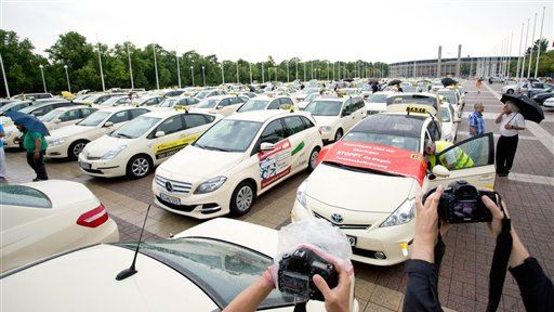 In this June 11, 2014, file photo, taxi drivers gather after a protest drive against the competition from Internet and mobile applications designed for calling cabs in Berlin.