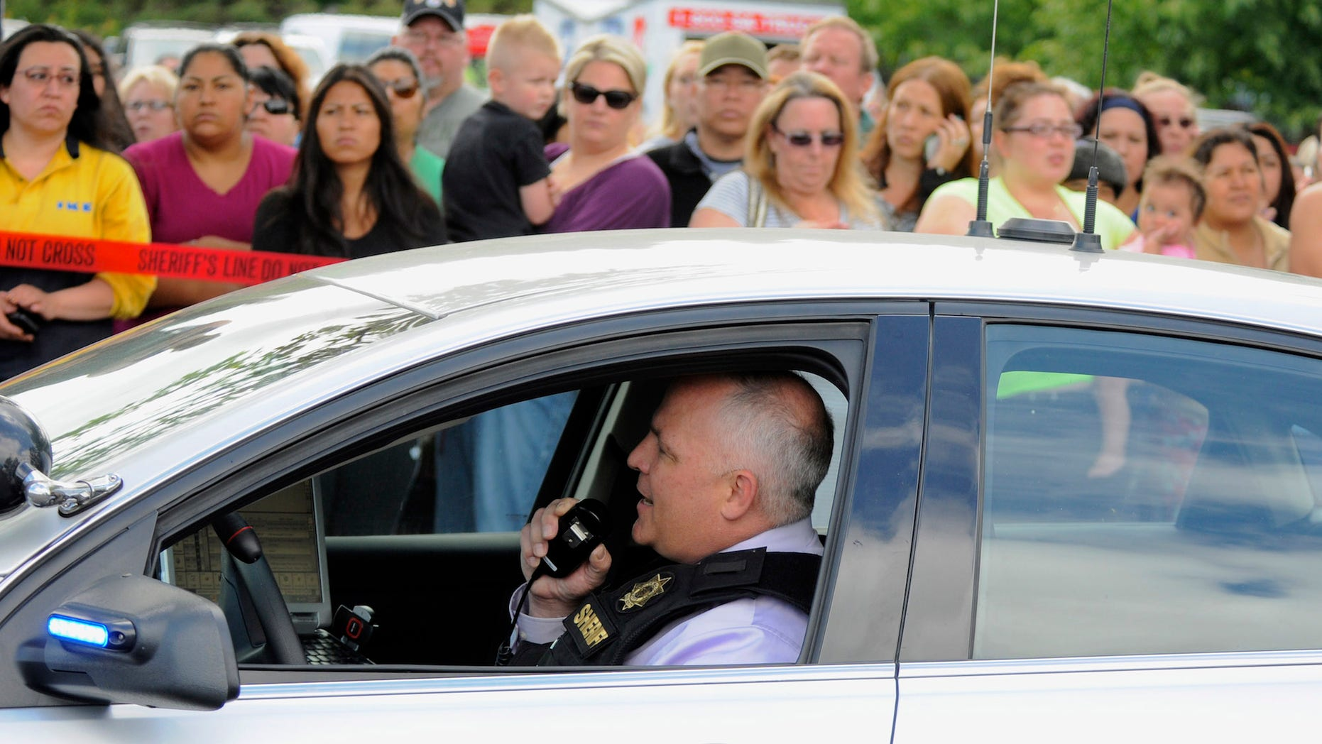 In this June 10, 2014, file photo, a sheriff's deputy talks on his radio as parents wait to be reunited with their children at a shopping center parking lot in Wood Village, Ore., after a shooting at Reynolds High School in Troutdale, Ore.