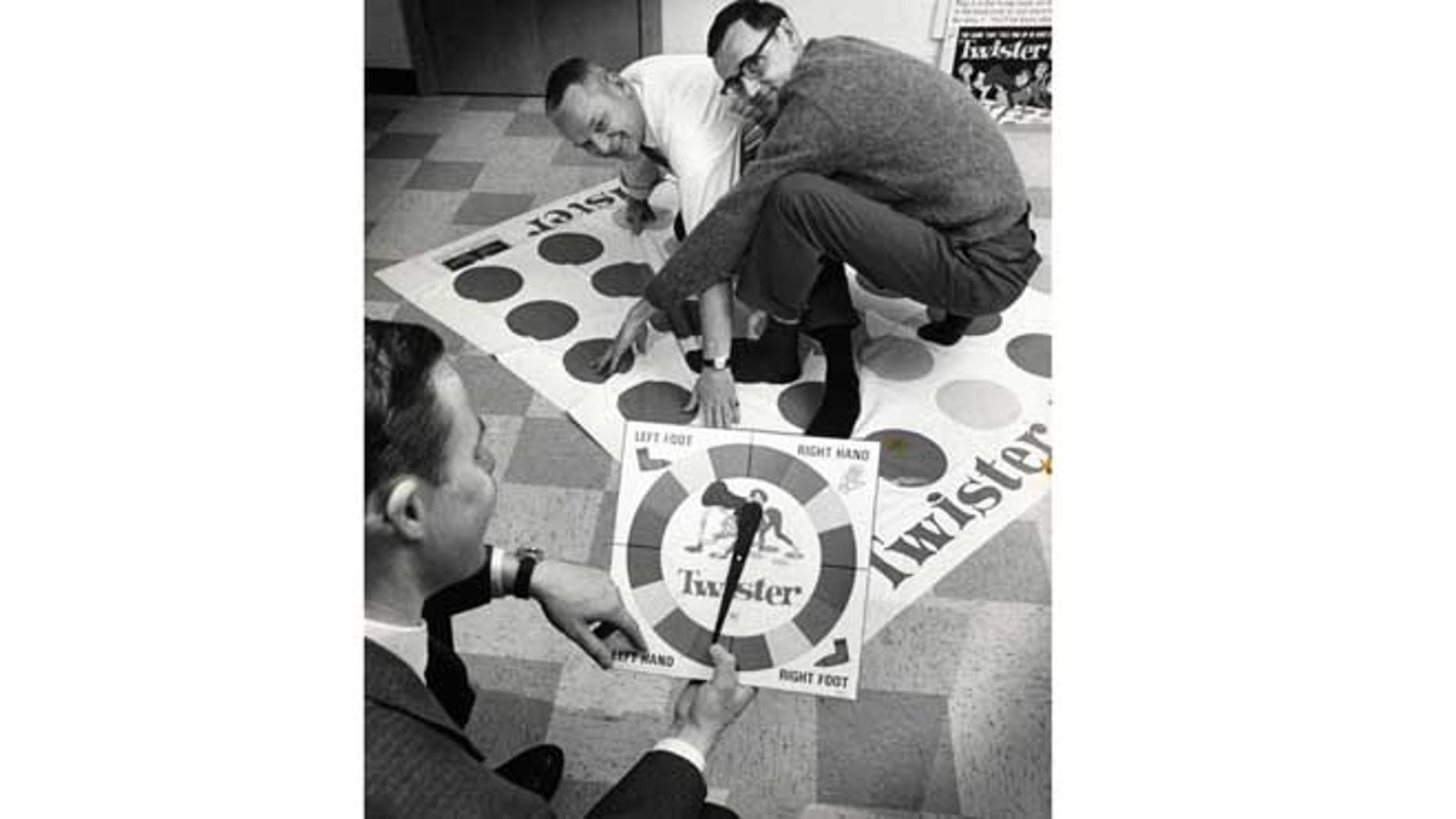 """Dec. 16,1966: In this photo, co-inventors of the game """"Twister"""" Charles Foley, left, and Neil Rabens demonstrate the game for Charles McCarty, foreground, president of Research and Development, Inc., in Minnesota."""