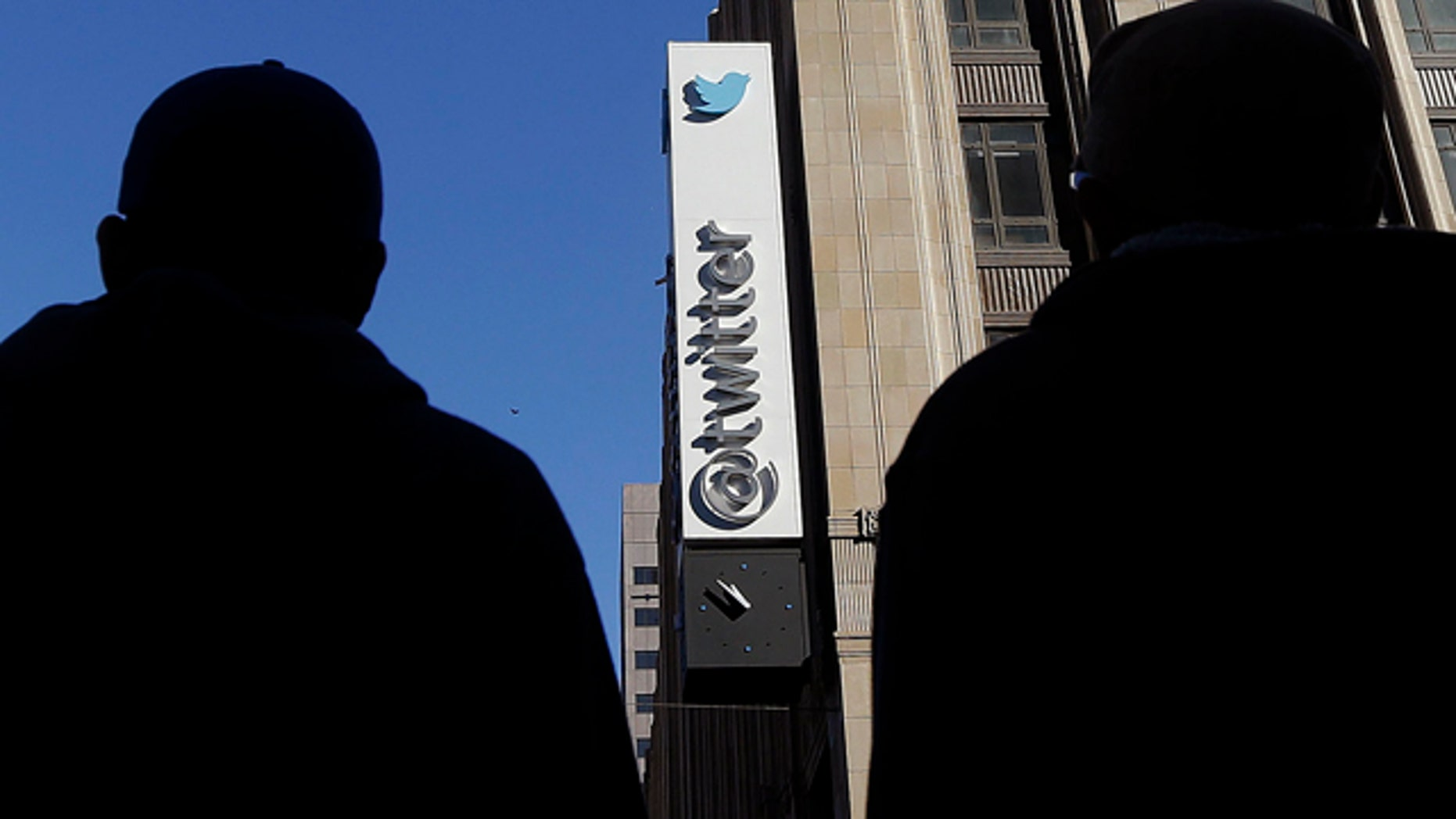 FILE - In this Monday, Nov. 4, 2013, file photo, pedestrians cross the street in front of Twitter headquarters in San Francisco. (AP Photo/Jeff Chiu, File)