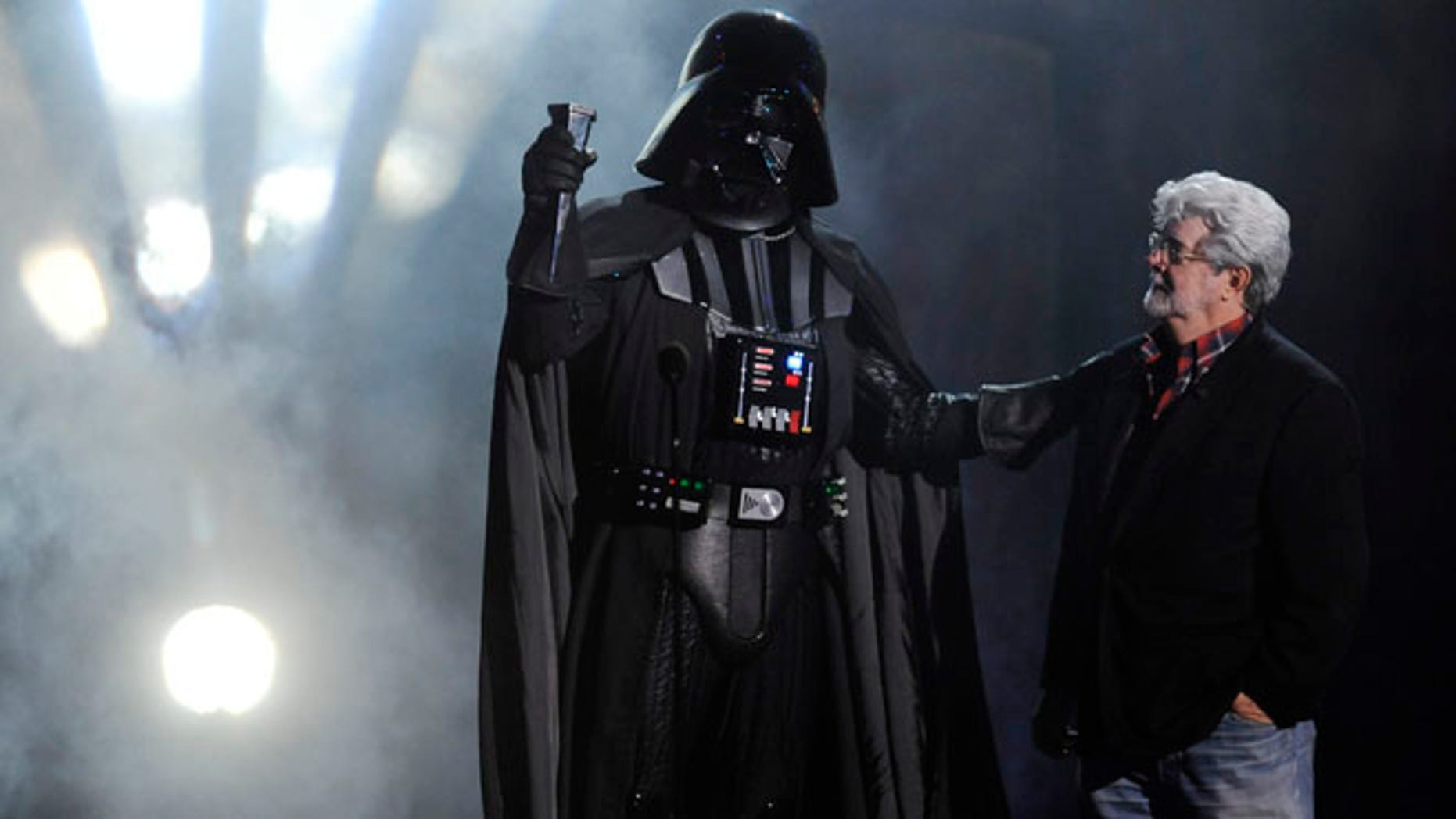 """Oct. 15, 2011: In this file photo, """"Darth Vader"""" accepts the Ultimate Villain award from """"Star Wars"""" creator George Lucas during the 2011 Scream Awards, in Los Angeles."""