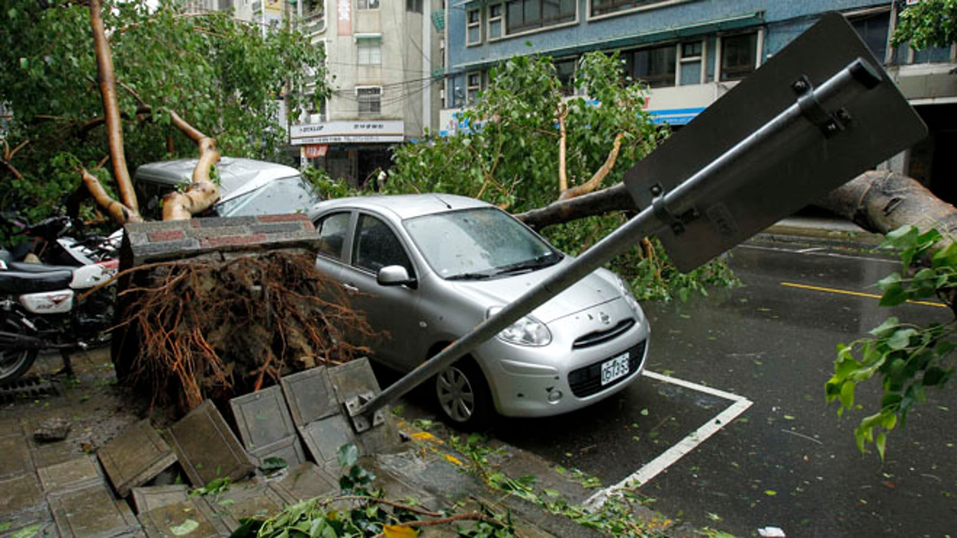 July 13, 2013: Fallen trees damaging vehicles lie on a street after Typhoon Soulik hit Taiwan in Taipei.