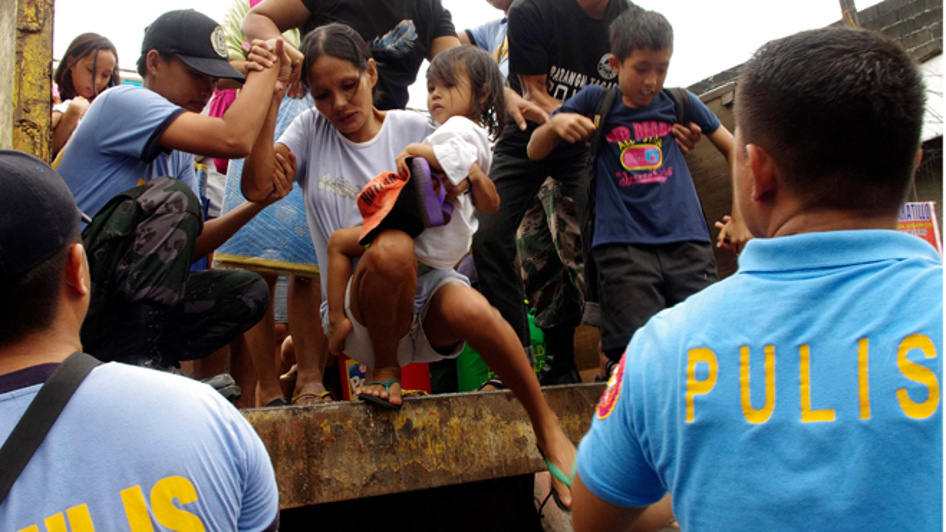 FILE: Nov. 7, 2013 Residents living near the slopes of Mayon volcano are evacuated to public schools by police before Typhoon Haiyan struck.