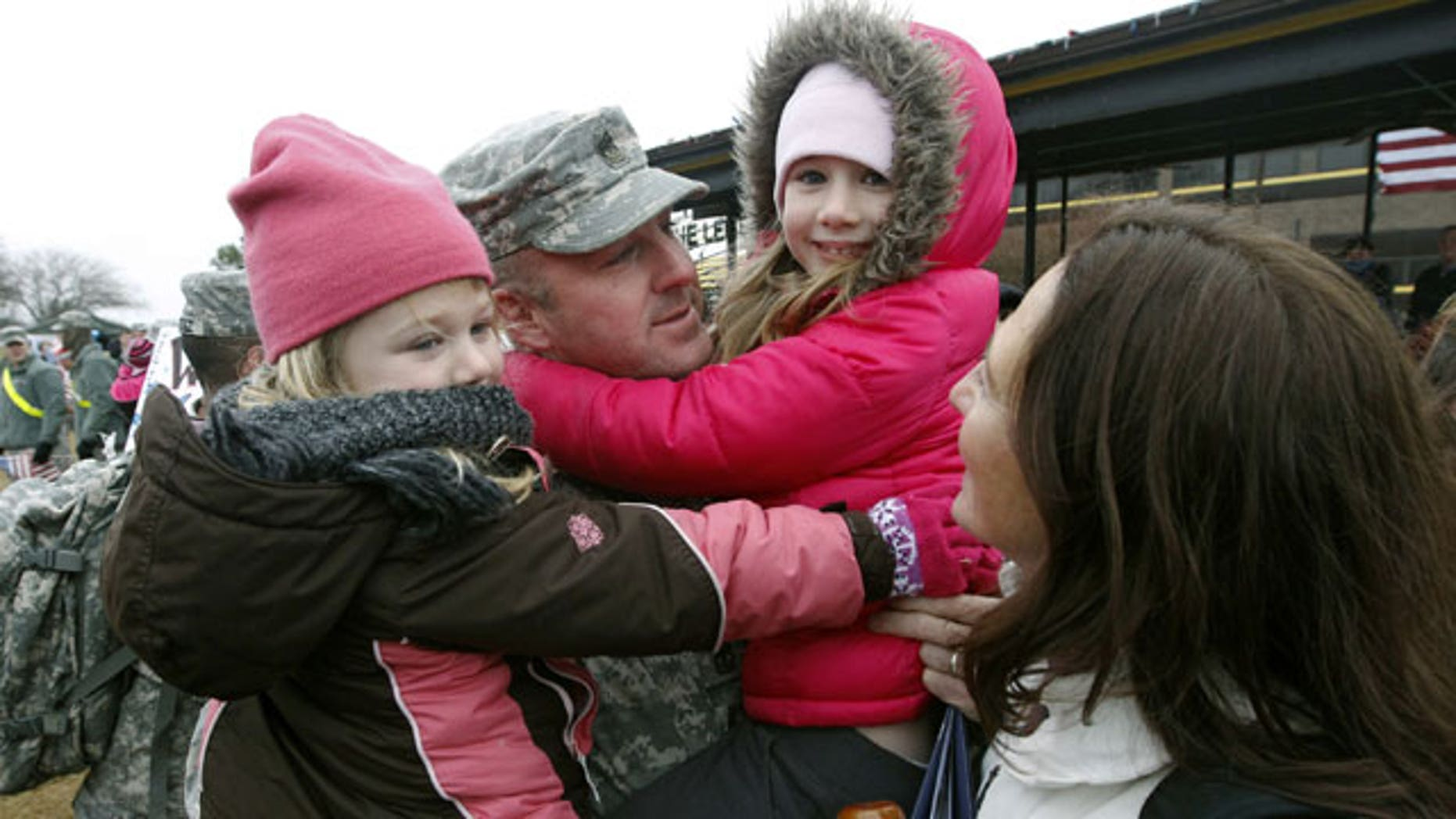 December 24, 2011: Sgt. Scott Dawson holds his daughters Mia, 5, left, and Victoria, 7, with his wife, Capt. Jessica Dawson, as U.S. Army 1st Cavalry 3rd Brigade soldiers return home from deployment in Iraq, on Christmas Eve at Fort Hood, Texas.