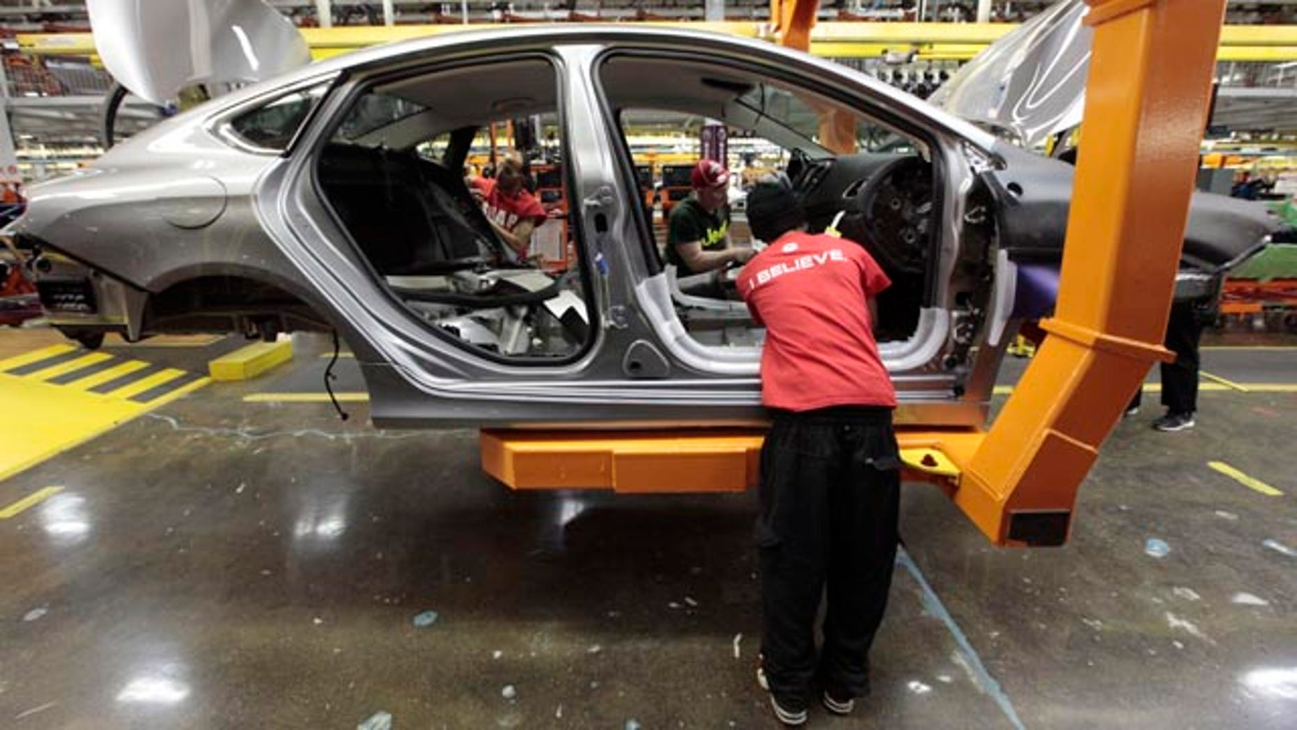 FILE - In this March 14, 2014 file photo, assembly line workers build a 2015 Chrysler 200 automobile at the Sterling Heights Assembly Plant in Sterling Heights, Mich. (AP Photo/Paul Sancya, File)