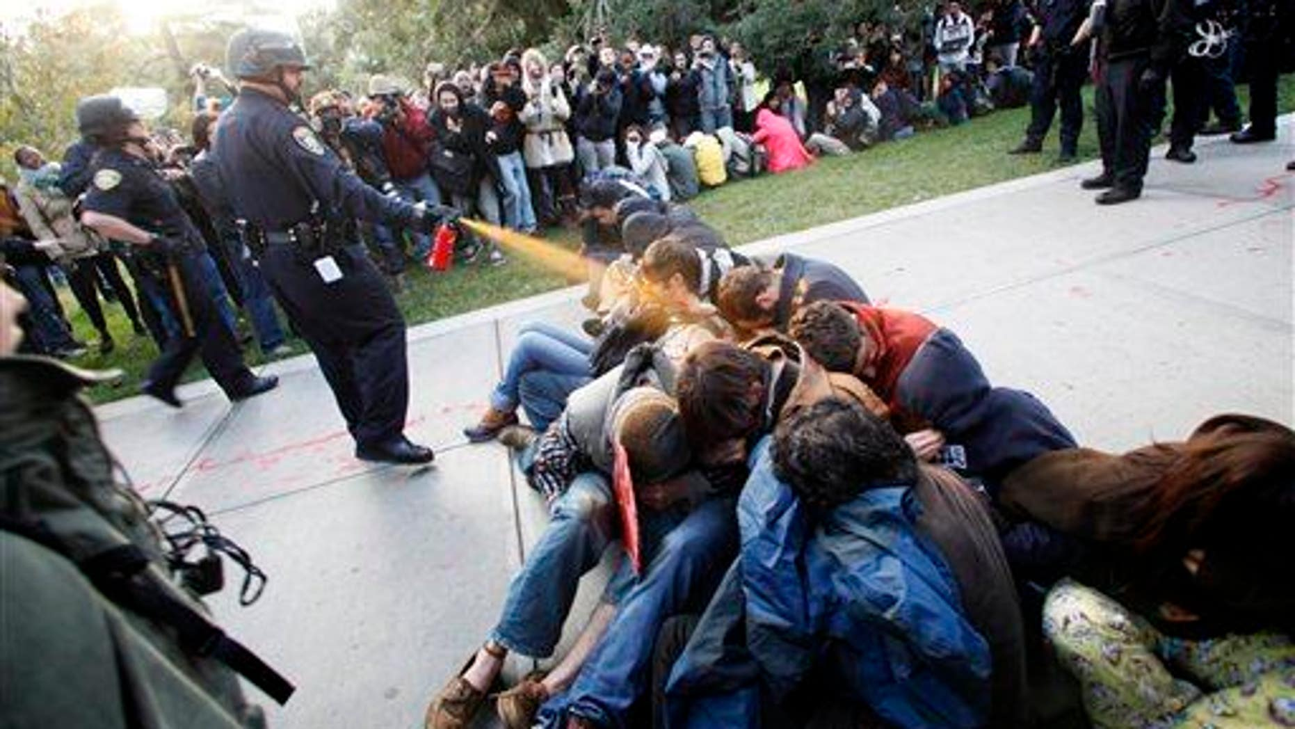 In this Nov. 18, 2011, file photo, University of California-Davis Police Lt. John Pike uses pepper spray on Occupy UC Davis protesters.