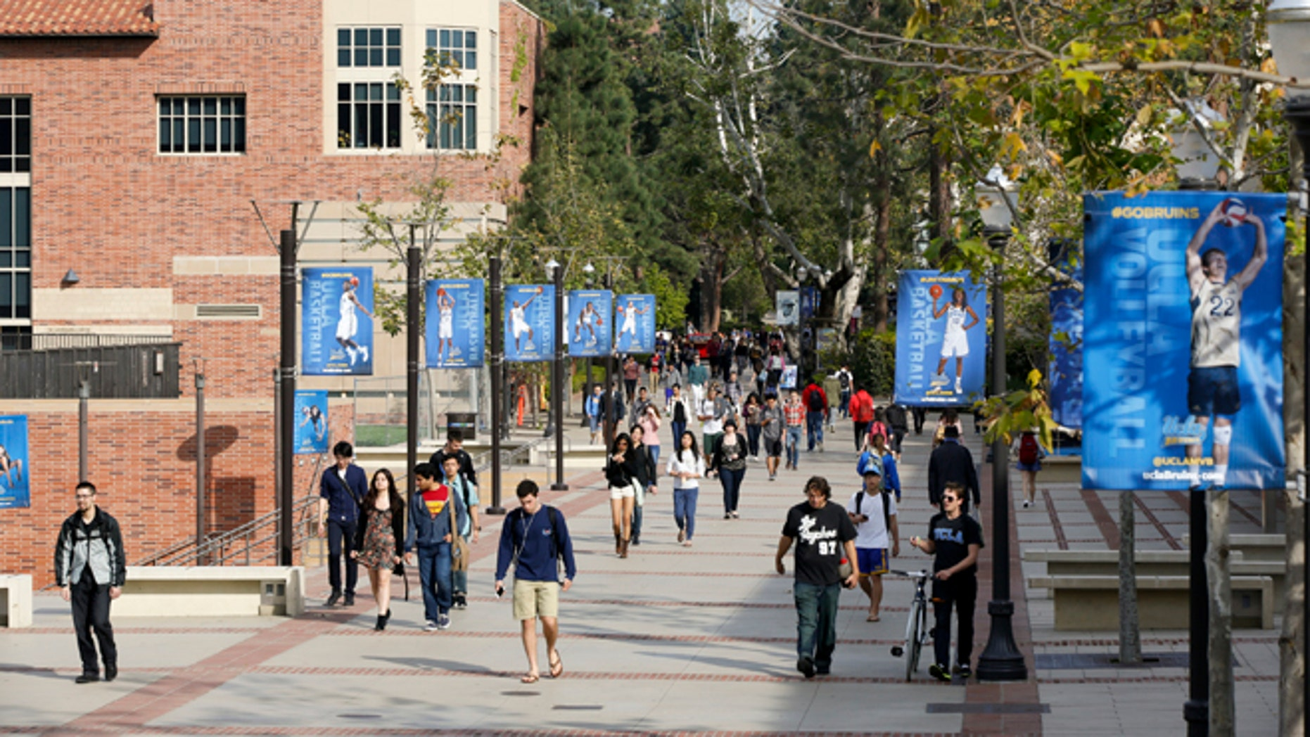 FILE - In this Feb. 26, 2015 file photo, students walk on the UCLA campus in Los Angeles. Fewer California high school students have been offered admission to University of California campuses for the fall, officials reported Thursday, July 2, 2015, while the number accepted from outside the state and abroad has again increased.  (AP Photo/Damian Dovarganes, File)